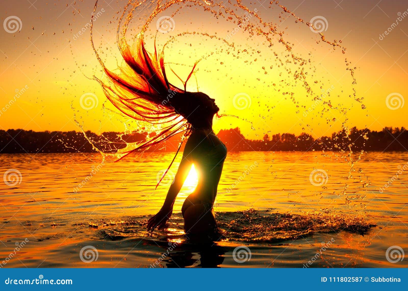 Καταβρέχοντας νερό κοριτσιών ομορφιάς πρότυπο με την τρίχα της Σκιαγραφία κοριτσιών πέρα από τον ουρανό ηλιοβασιλέματος Κολύμβηση
