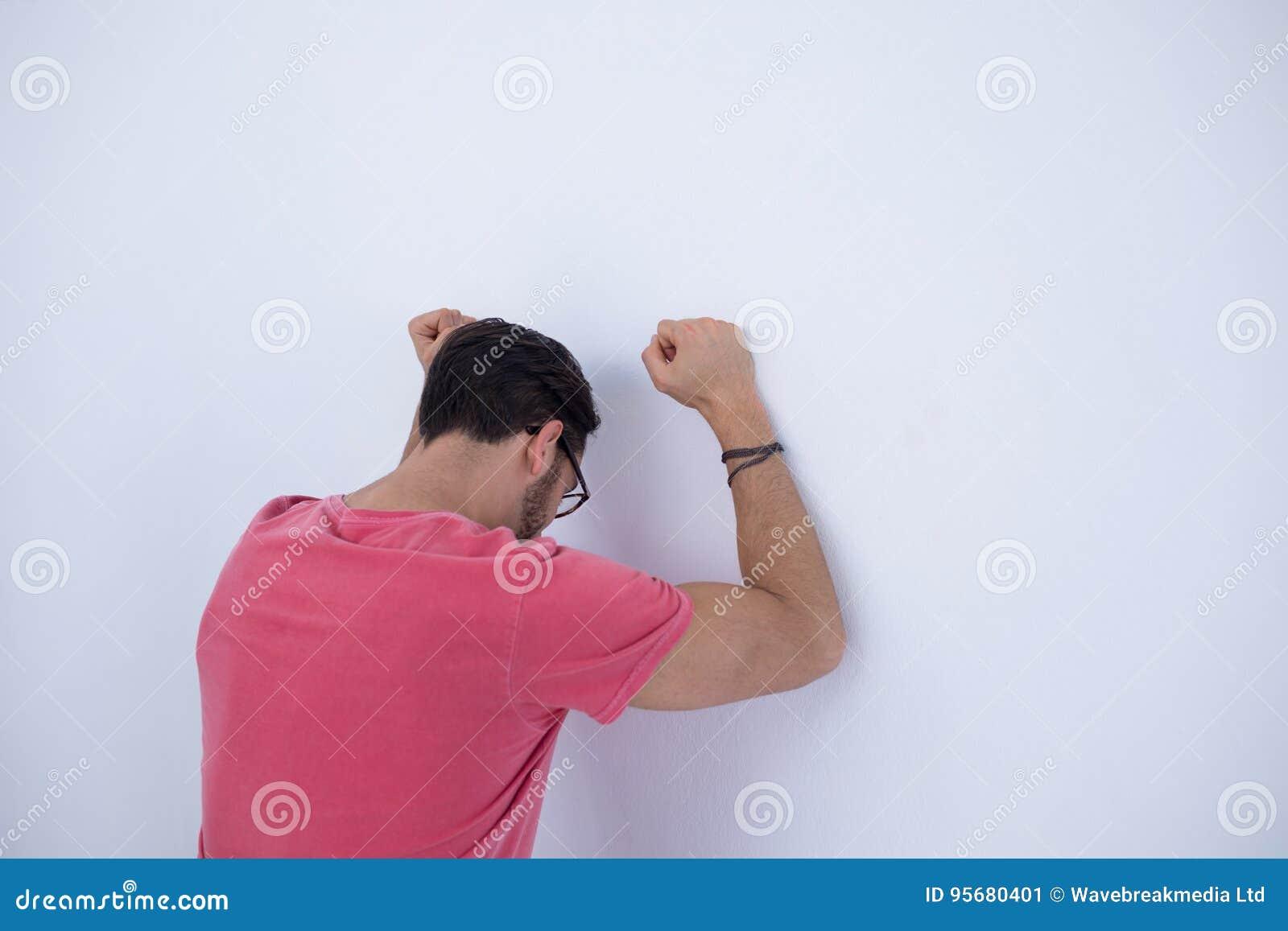 Καταθλιπτικός αρσενικός ανώτερος υπάλληλος με τα όπλα που αυξάνονται κλίση στον τοίχο
