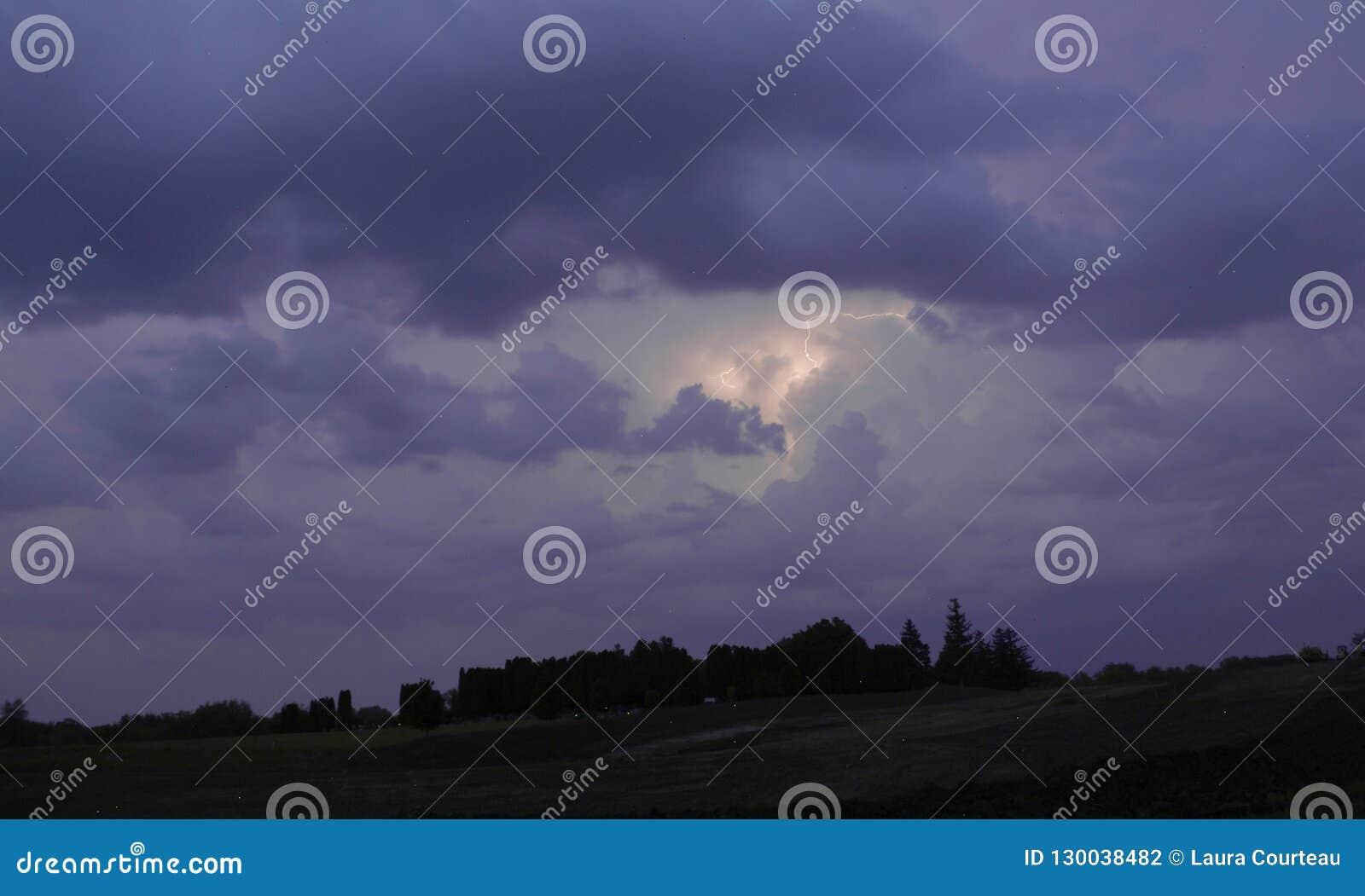 Καταιγίδα με την αστραπή στη μέση του πορφυρού ουρανού επάνω από τα σκοτεινά δέντρα σε Μινεσότα