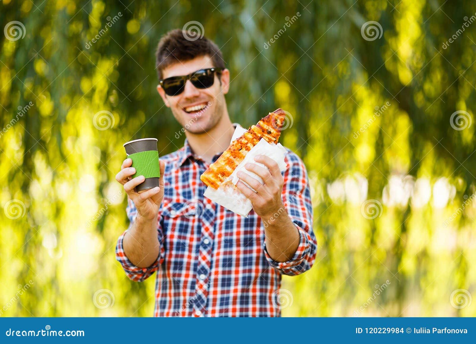 κατανάλωση της πίτσας ατόμ&o Ο εύθυμος νέος τύπος τρώει τον καφέ κατανάλωσης πιτσών στο πάρκο