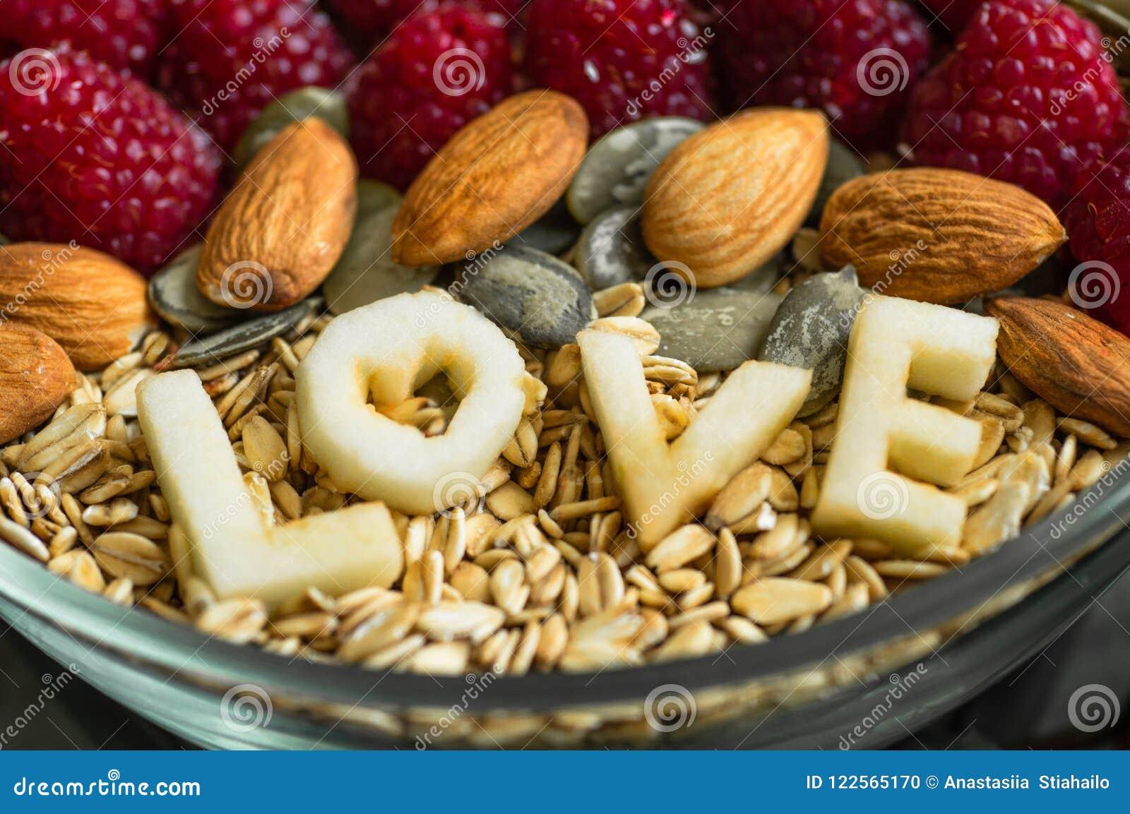 Κατανάλωση του υγιούς κύπελλου προγευμάτων Η ΑΓΑΠΗ λέξης σε ένα πιάτο με ένα υγιές γεύμα Σμέουρο, μπανάνα, καρύδια Χορτοφάγος ένν