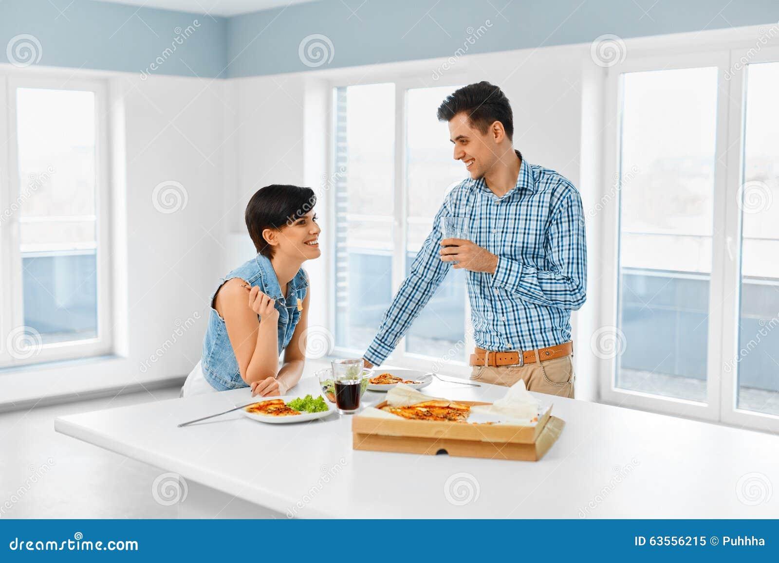 Κατανάλωση των τροφίμων Ευτυχές καλό ζεύγος που τρώει την πίτσα στο εσωτερικό Ελεύθερος χρόνος Γ