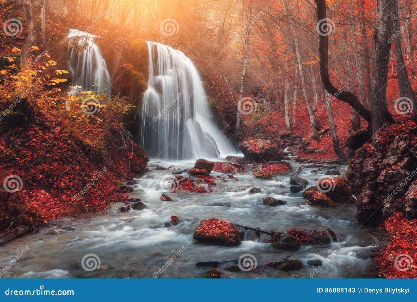 Καταρράκτης στον ποταμό βουνών στο δάσος φθινοπώρου στο ηλιοβασίλεμα
