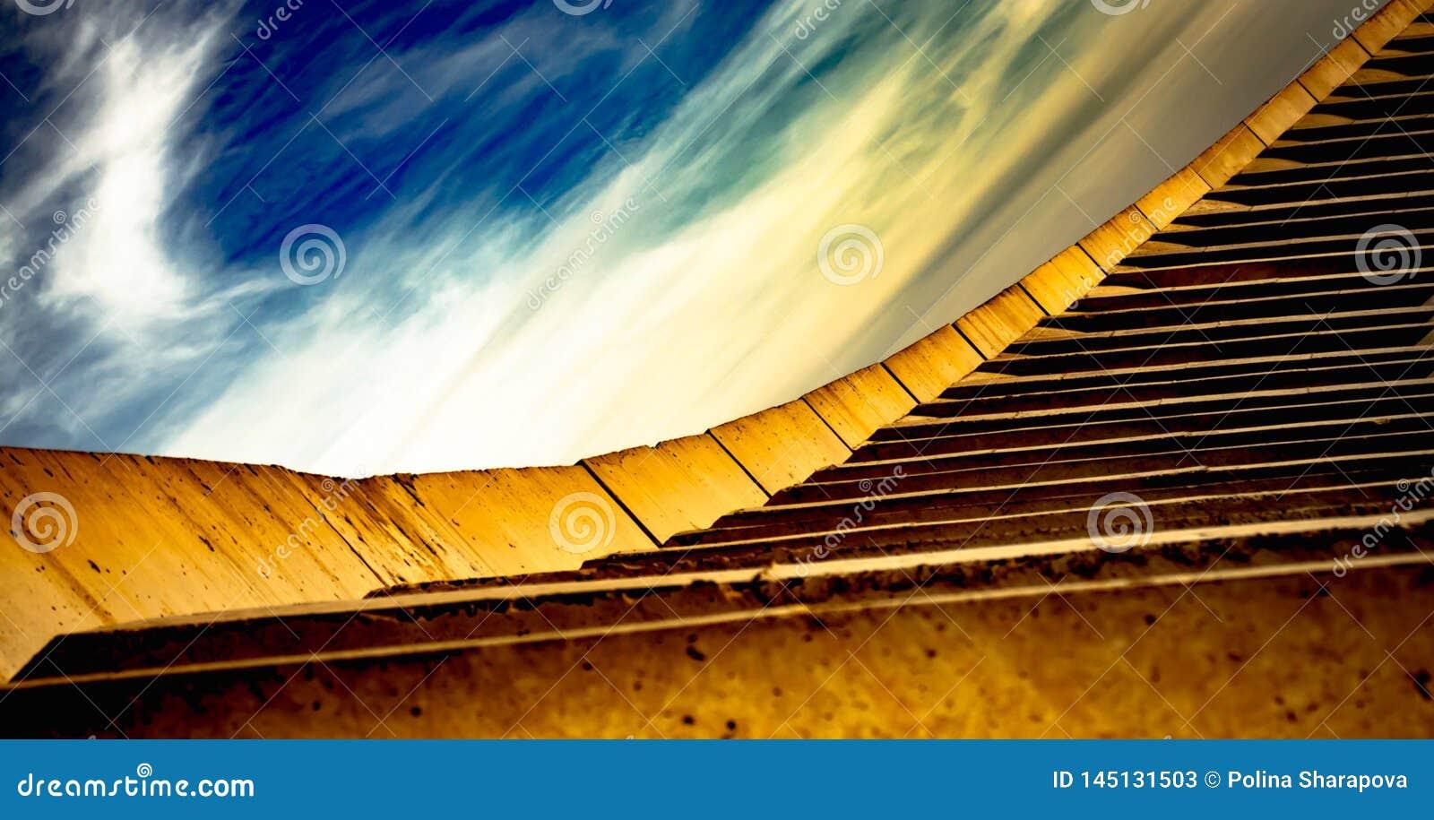 Κατασκευή, αφηρημένα κίτρινα σκαλοπάτια και όμορφος ουρανός με τα άσπ