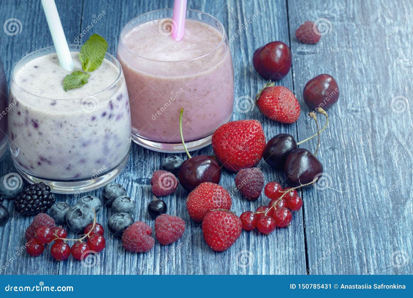 Καταφερτζής σμέουρων, φραουλών και βακκινίων στο μπλε ξύλινο υπόβαθρο milkshake με τα φρέσκα μούρα γιαούρτι μούρων με