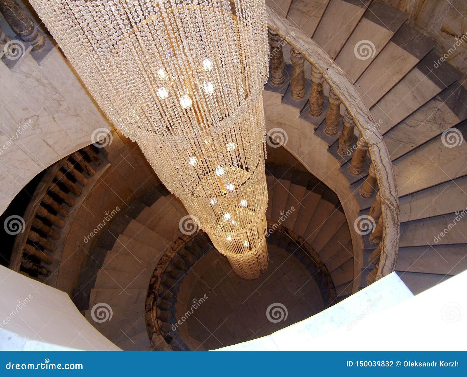 Κατώτατο σημείο άποψης επάνω στην όμορφη σκάλα πολυτέλειας με τα ξύλινα κιγκλιδώματα