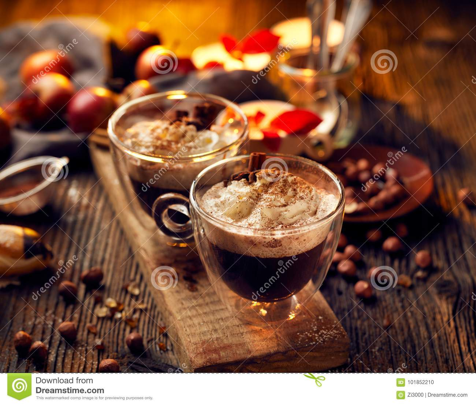 Καυτή σοκολάτα με την κτυπημένη κρέμα, που ψεκάζεται με την αρωματική κανέλα στα φλυτζάνια γυαλιού