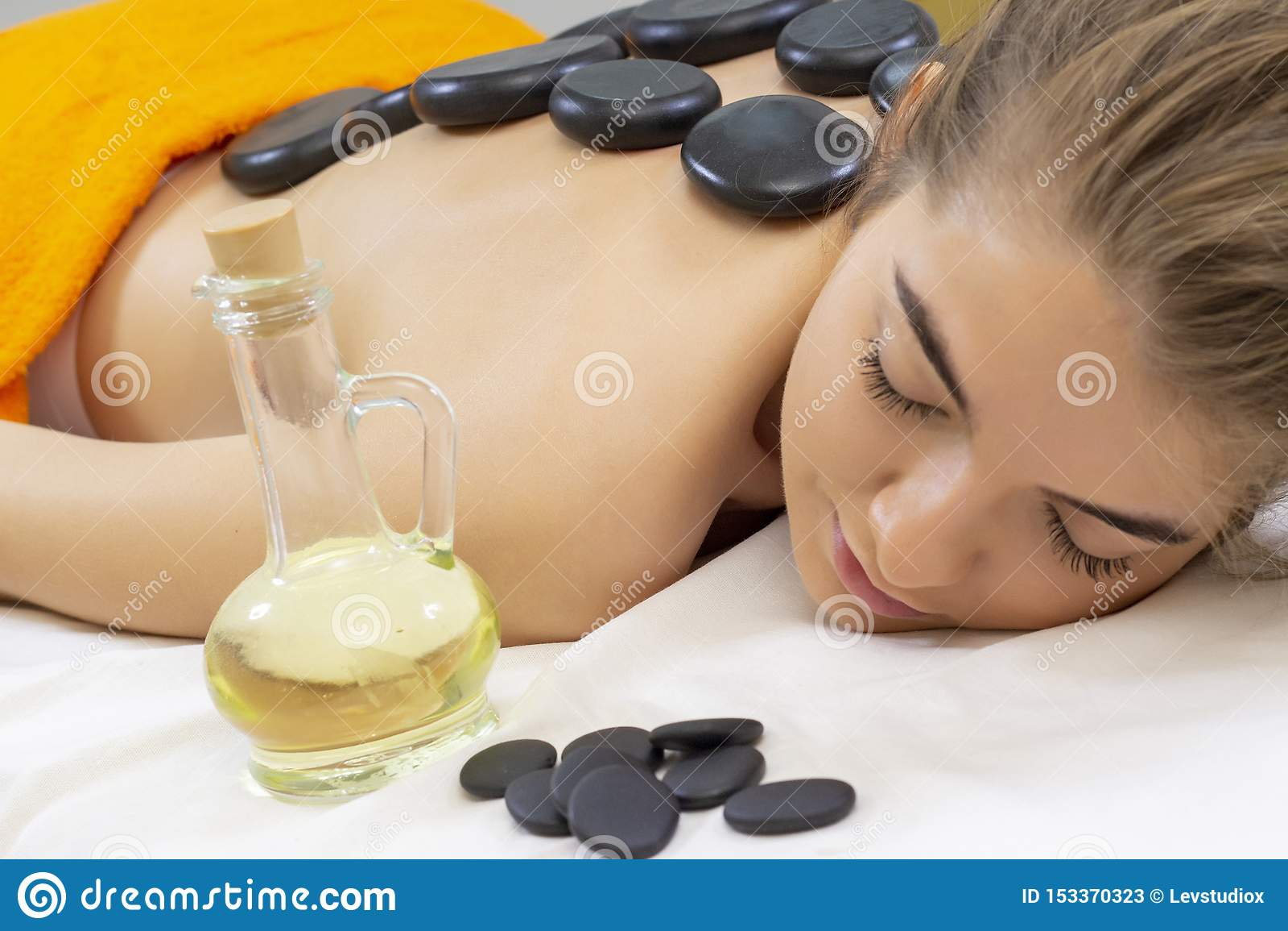 Καυτό μασάζ πετρών SPA Επαγγελματικό beautician που τρίβει το θηλυκό πίσω από τις πέτρες