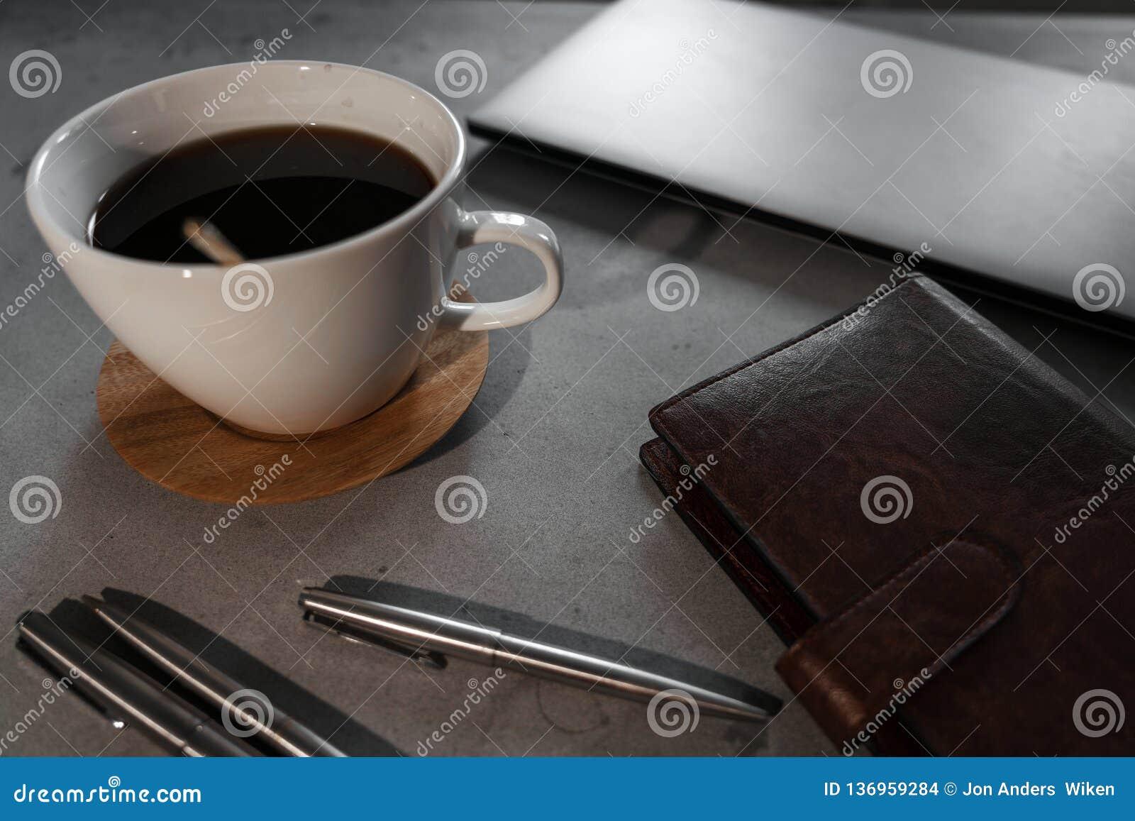 Καφές, κουτάλι, lap-top, σημειωματάριο και μάνδρες στο συγκεκριμένο πίνακα