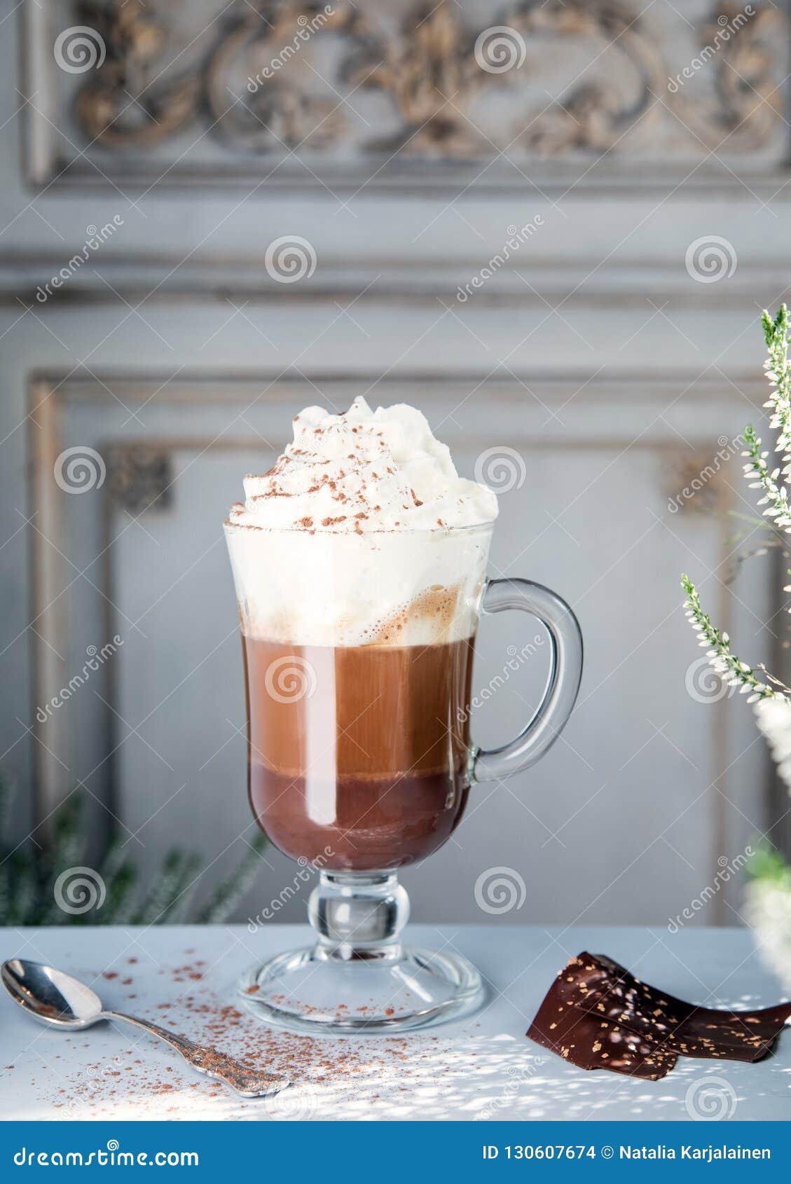 Καφές με τη σοκολάτα και κτυπημένη κρέμα σε ένα διαφανές γυαλί στα πλαίσια ενός εκλεκτής ποιότητας τοίχου