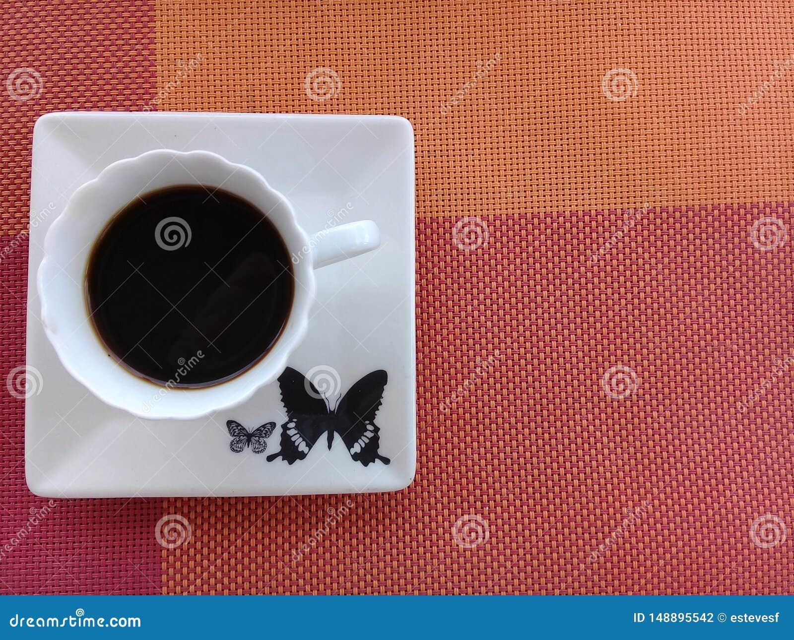 Καφές πάνω από ένα πιατάκι με το σχέδιο πεταλούδων