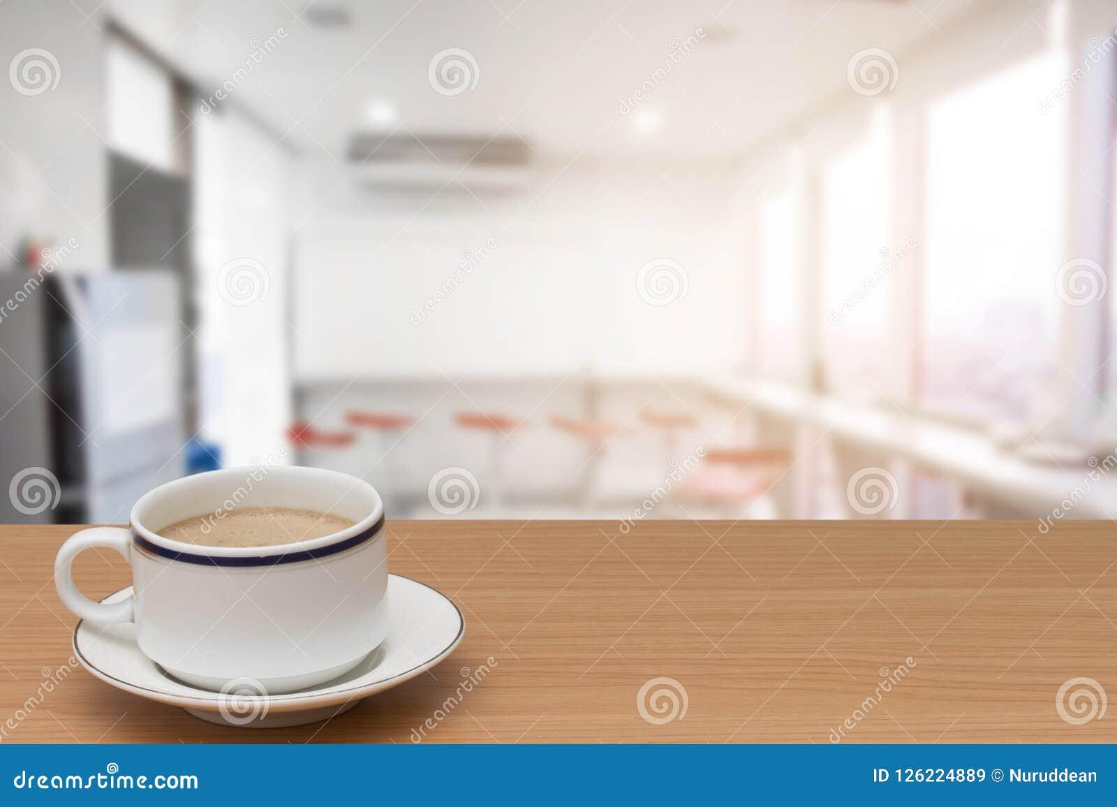 Καφές στον ξύλινο πίνακα με θολωμένος του σύγχρονου εσωτερικού κουζινών για το υπόβαθρο