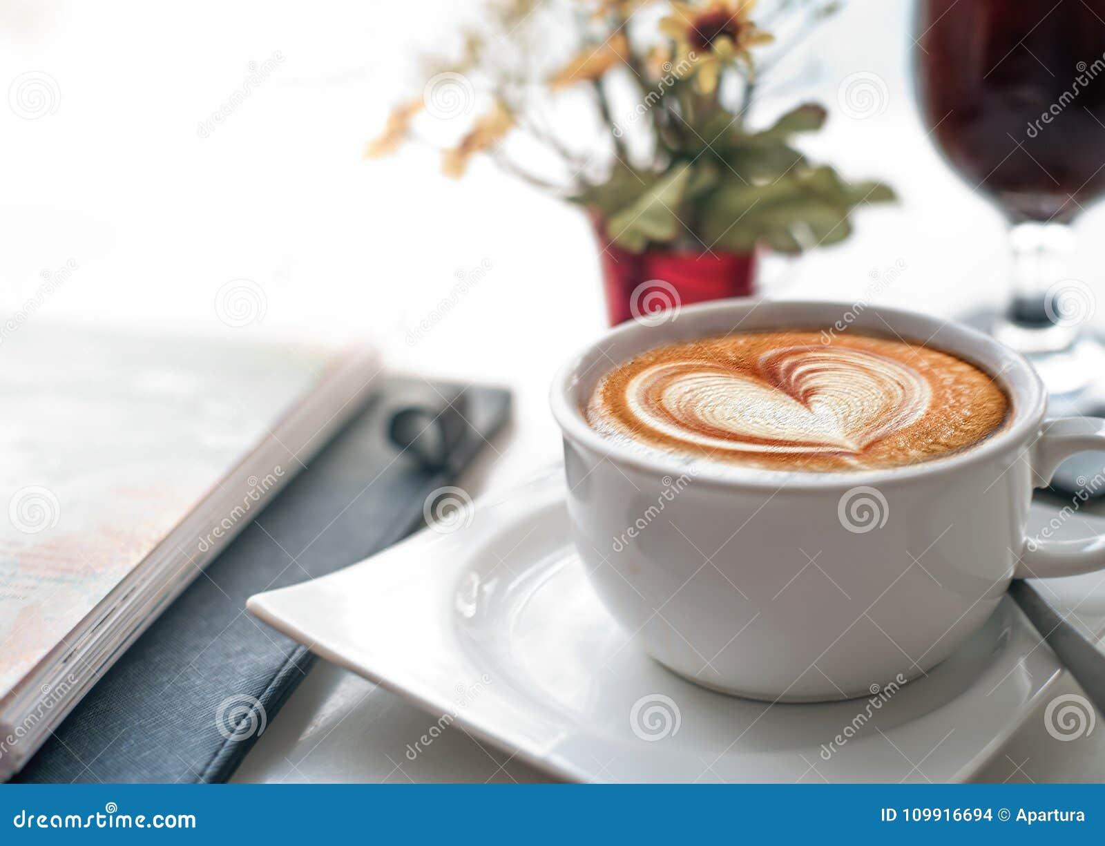Καφές στο λειτουργώντας γραφείο κατά τη διάρκεια της επιχειρησιακής συνεδρίασης με την τέχνη Latte μορφής καρδιών αγάπης