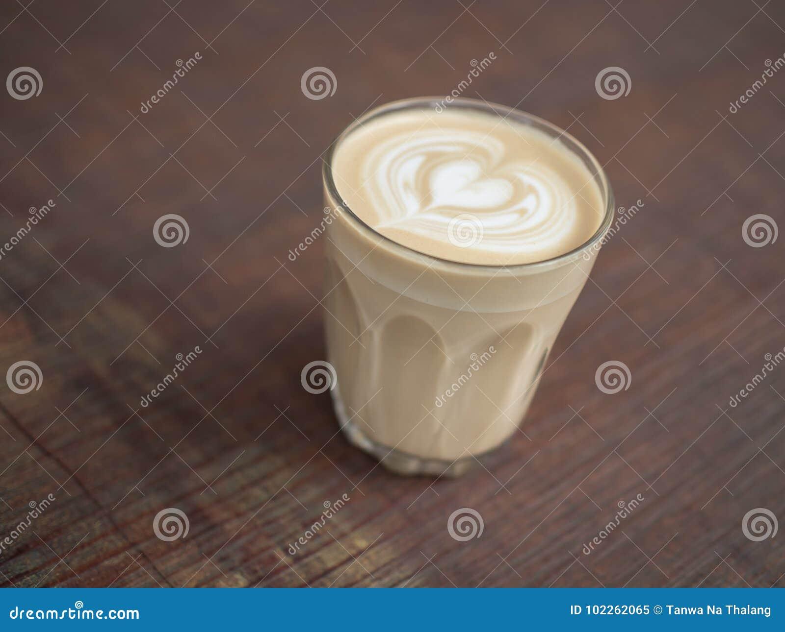 Καφές τέχνης Latte στο ξύλινο υπόβαθρο