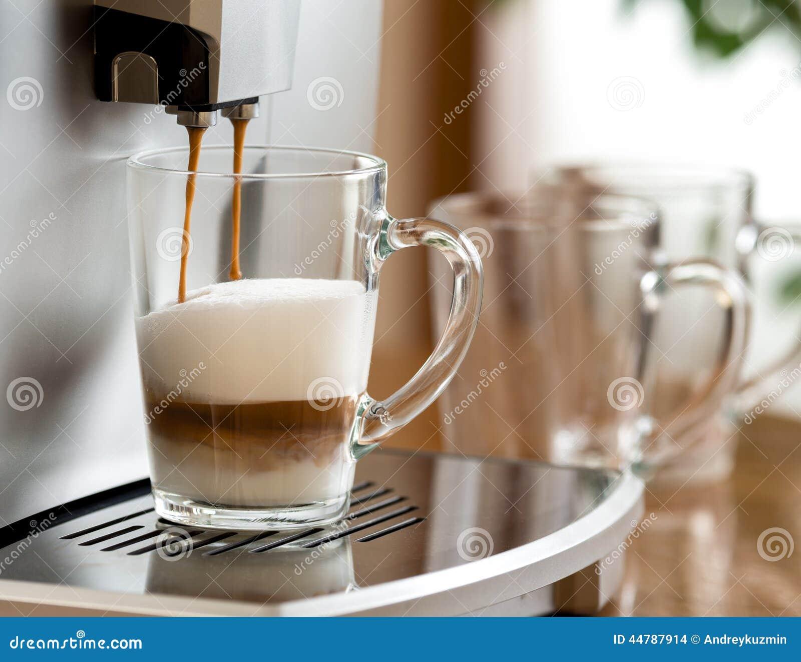 Καφές Cappuccino που προετοιμάζεται στο φλυτζάνι γυαλιού με τη μηχανή