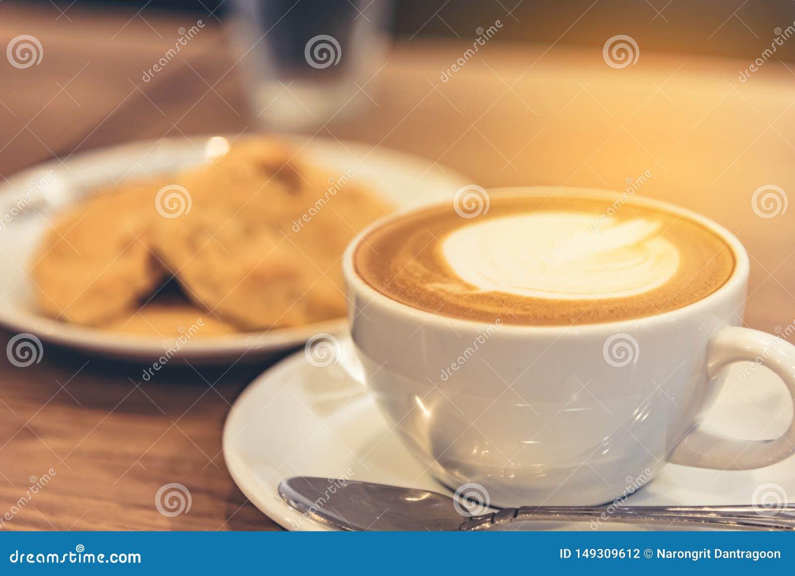 Καφές latte στο φλυτζάνι με το μπισκότο στον πίνακα