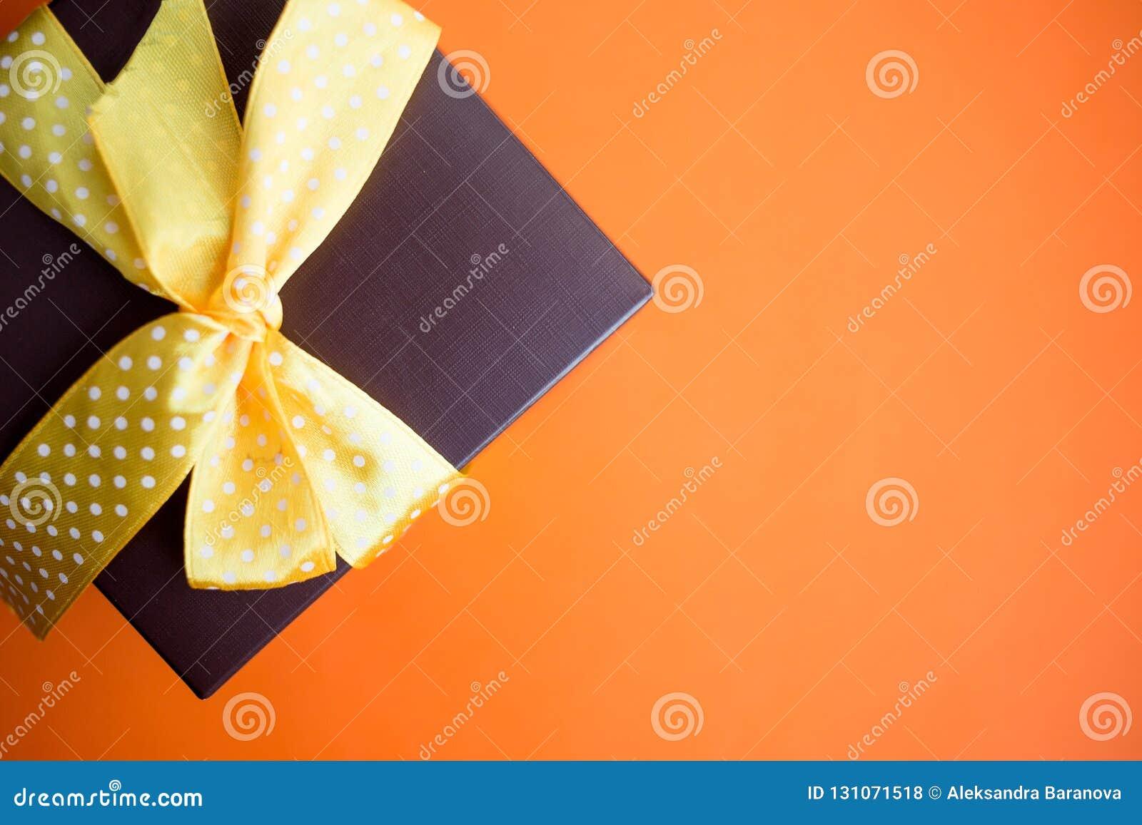 Καφετί κιβώτιο δώρων με την κίτρινη κορδέλλα στο πορτοκαλί υπόβαθρο Τοπ άποψη με το διάστημα αντιγράφων