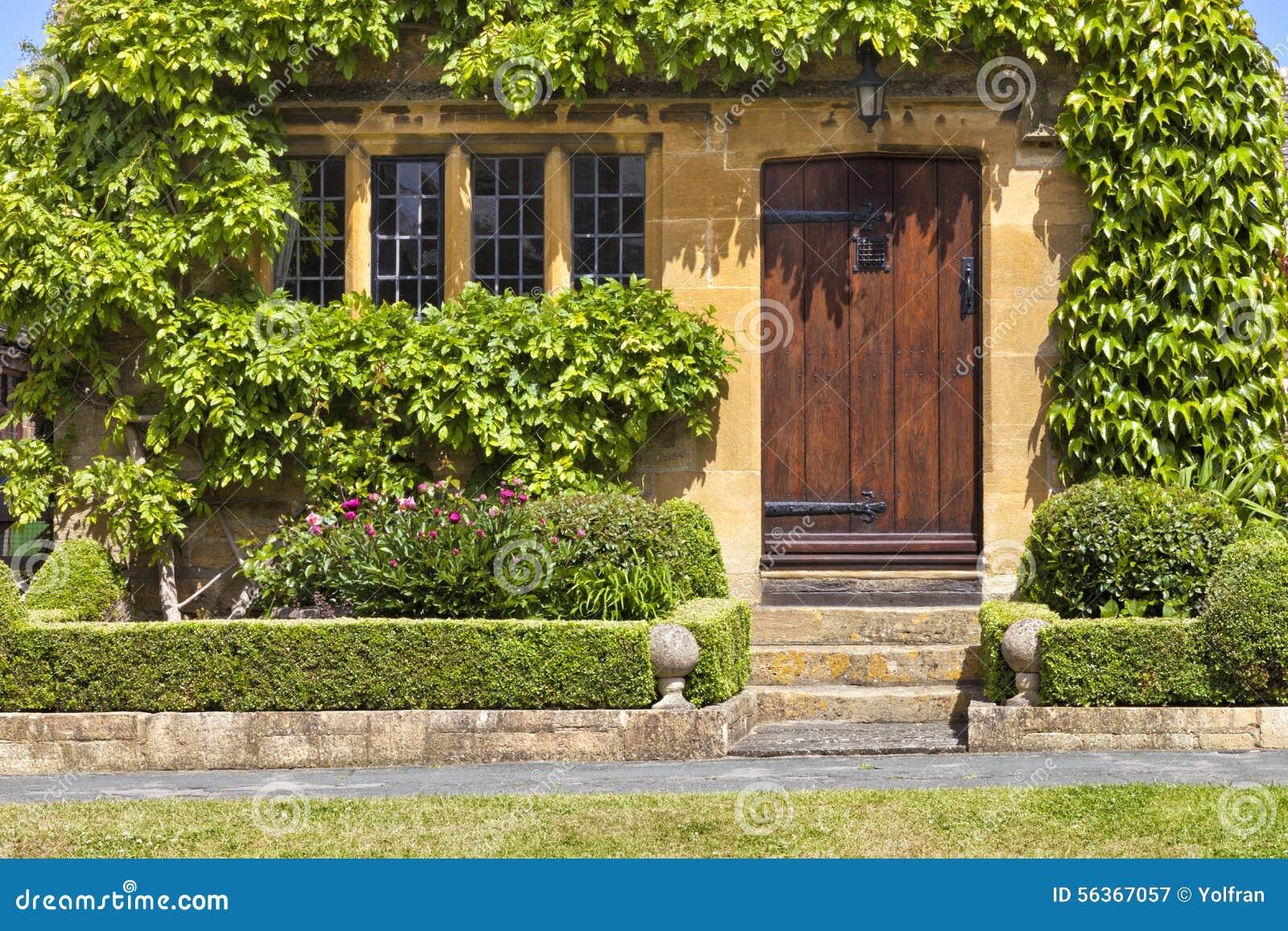 9f789d2737c9 Καφετιές ξύλινες πόρτες στο παραδοσιακό αγγλικό λιθοστρωμένο εξοχικό ...