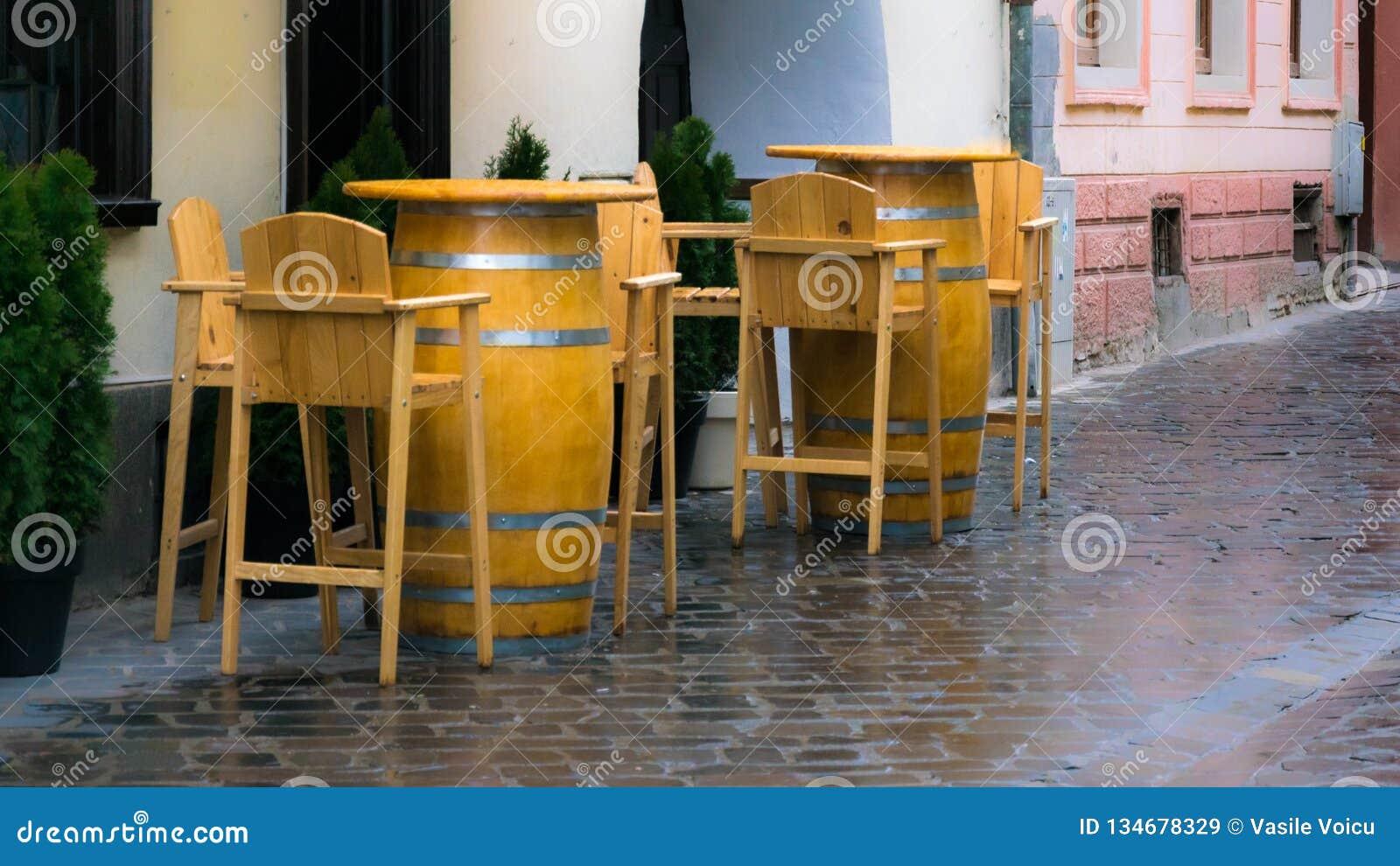 Κενά ξύλινα καρέκλες και επιτραπέζια βαρέλια στην οδό τη βροχερή ημέρα