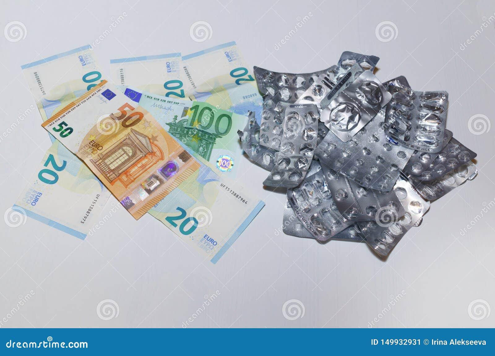 Κενές φουσκάλες από τα χάπια και ευρο- χρήματα σε ένα άσπρο υπόβαθρο Η έννοια του υψηλού κόστους των φαρμάκων