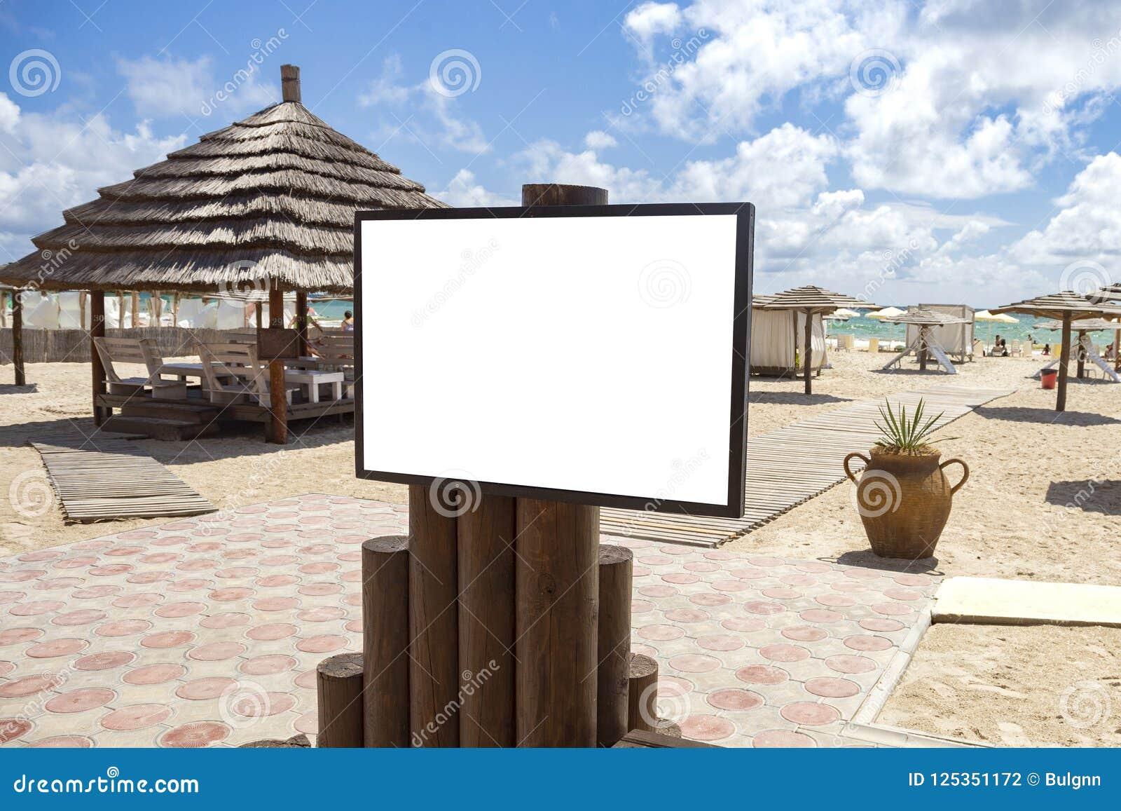 Κενή υπαίθρια διαφήμιση προτύπων με το διάστημα αντιγράφων στην παραλία κοντά στο τ