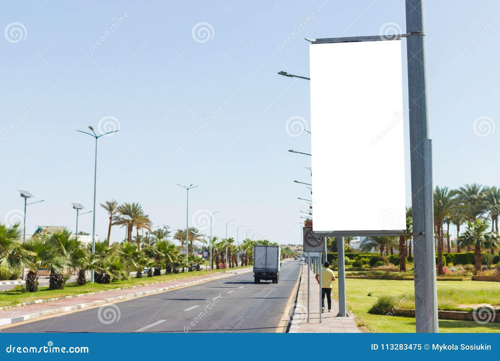 Κενή χλεύη επάνω του κάθετου πίνακα διαφημίσεων αφισών οδών στο υπόβαθρο πόλεων summmer