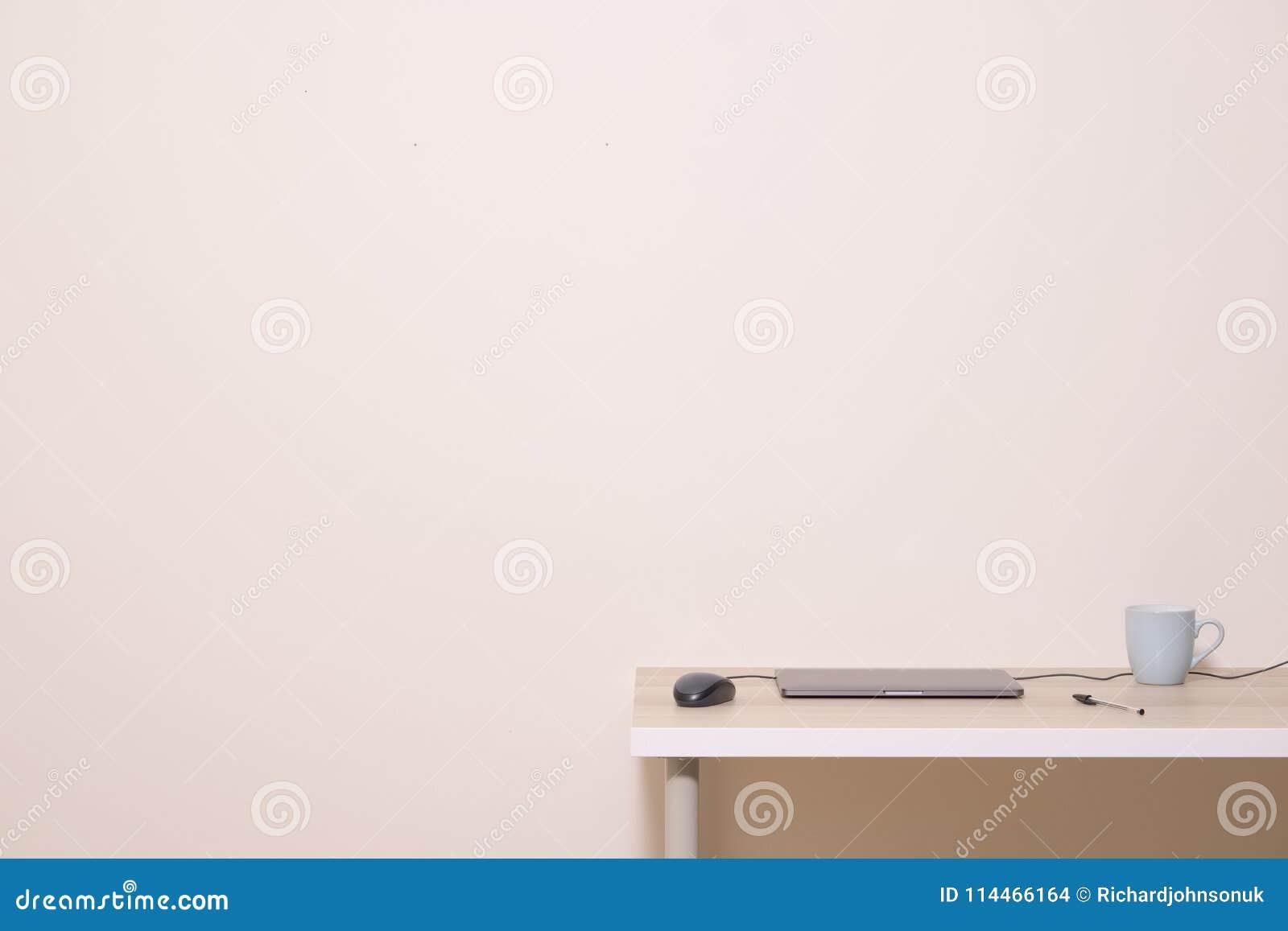 Κενός άσπρος τοίχος διαφημίσεων επάνω από το ουδέτερο κενό υπόβαθρο μανδρών ποντικιών lap-top φλυτζανιών εγχώριων γραφείων γραφεί