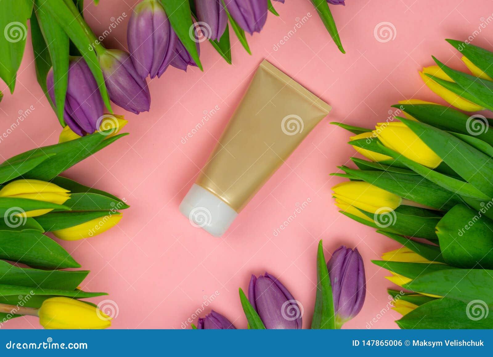 Κενός σωλήνας της κρέμας σε ένα ρόδινο υπόβαθρο με τα λουλούδια