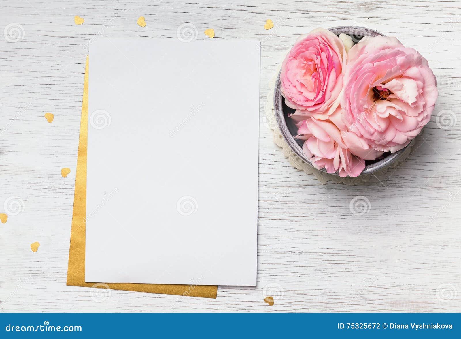 Κενό έγγραφο και χαριτωμένα ρόδινα λουλούδια στον άσπρο ξύλινο πίνακα