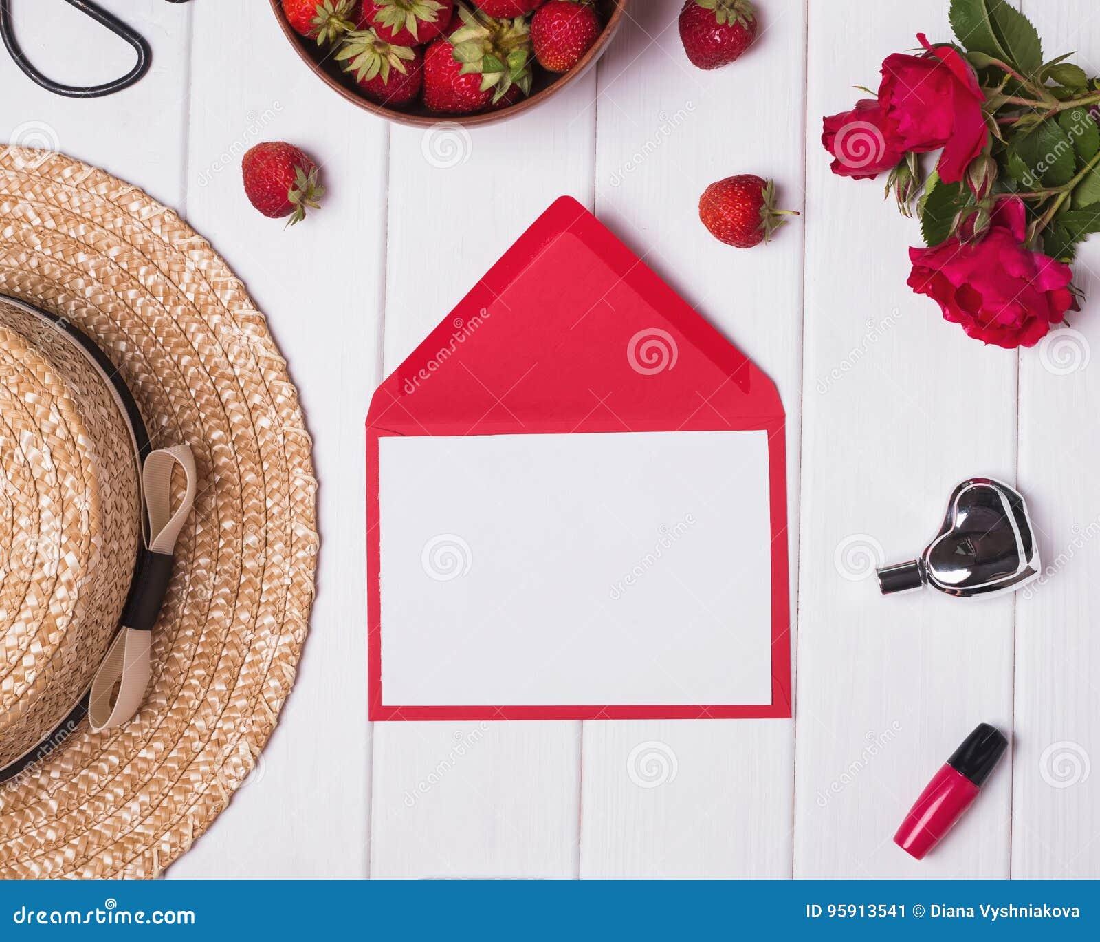 Κενό έγγραφο, καπέλο, κόκκινες τριαντάφυλλα και φράουλες στη λευκιά ξύλινη ΤΣΕ