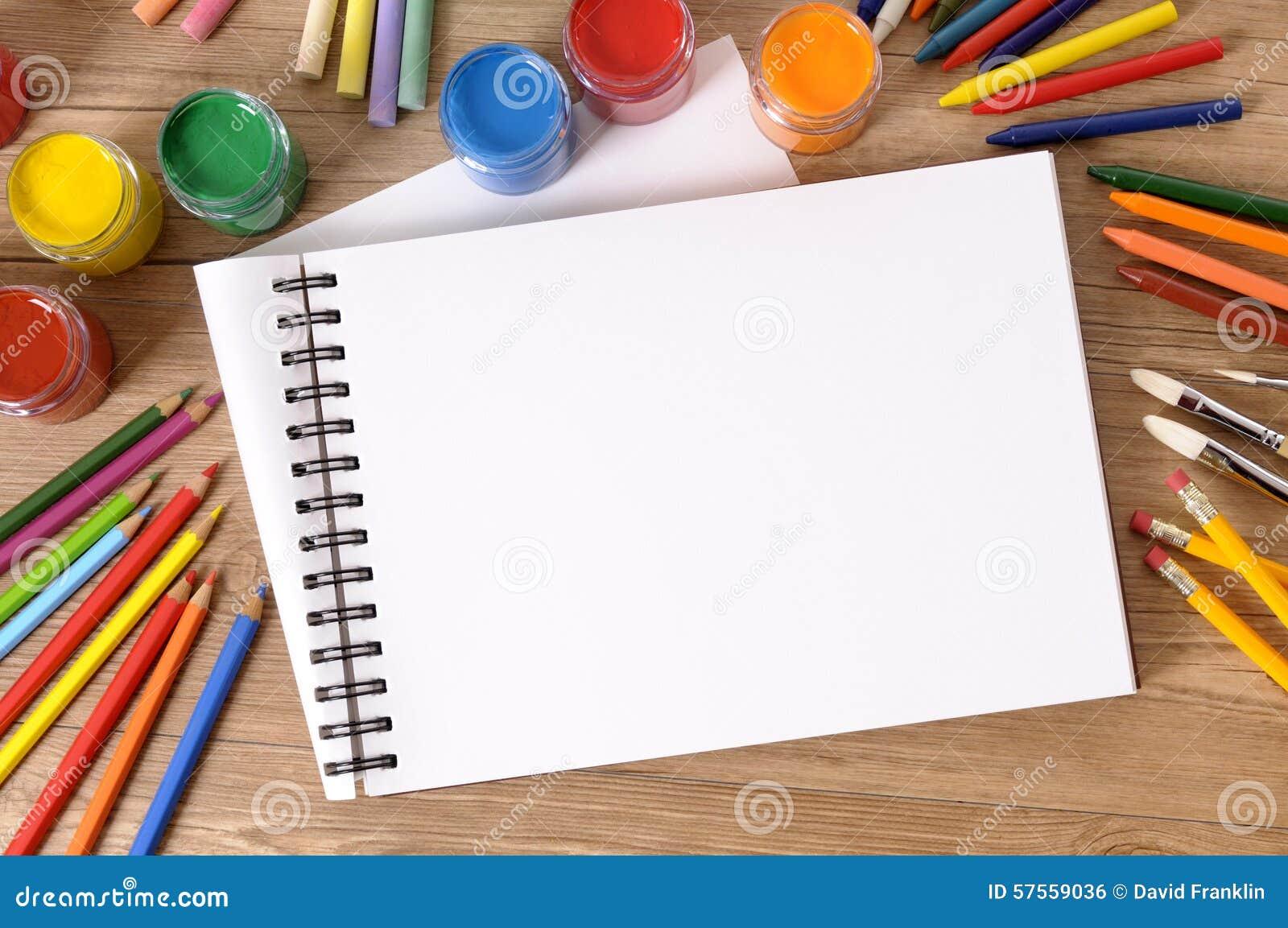 Κενό βιβλίο τέχνης ή μαξιλάρι σκίτσων με τον εξοπλισμό τέχνης, χρώματα στο σχολικό γραφείο, διάστημα αντιγράφων