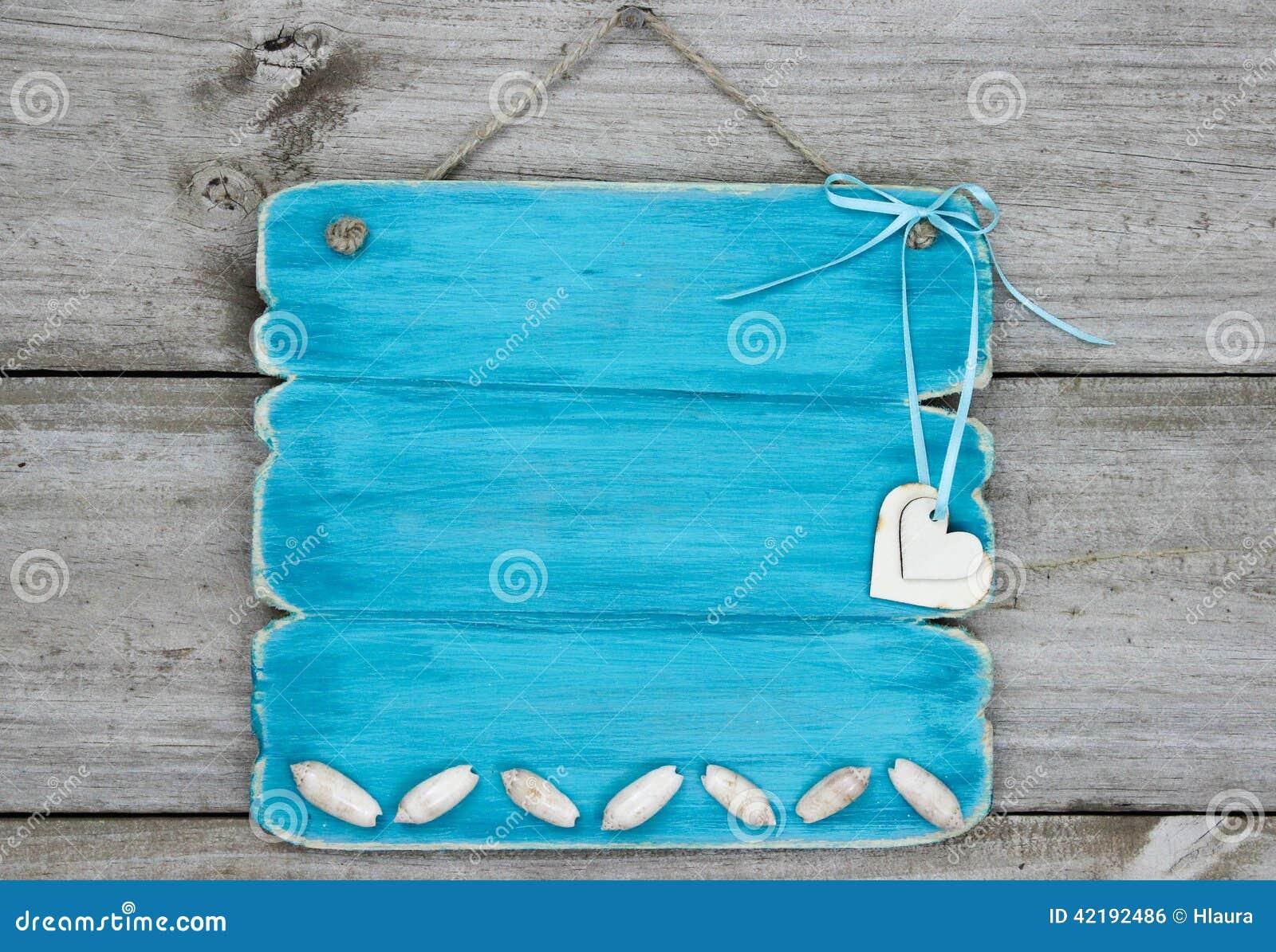 Κενό μπλε σημάδι κιρκιριών με τα θαλασσινά κοχύλια και τις καρδιές που κρεμούν στην αγροτική ξύλινη πόρτα