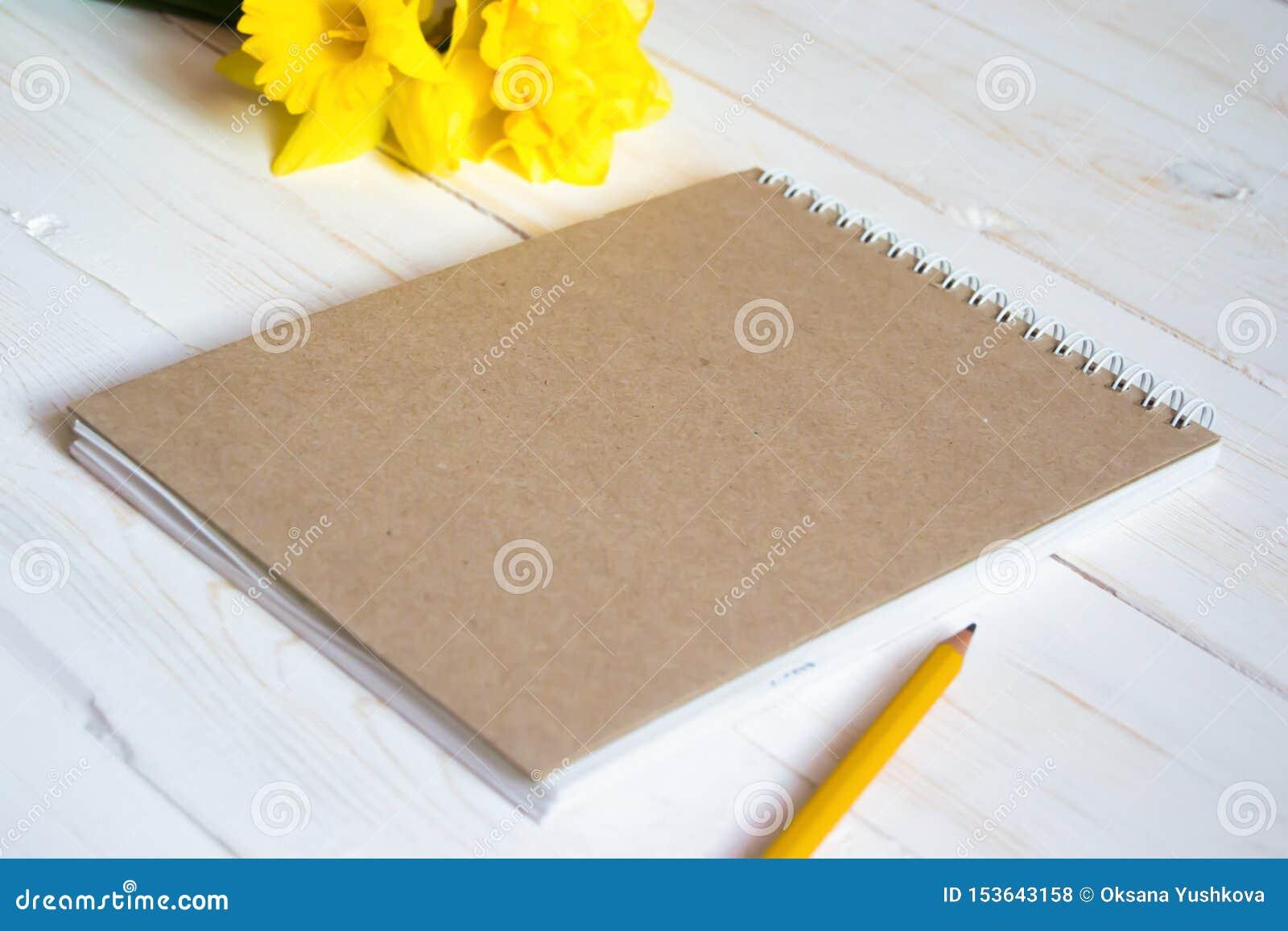 Κενό σημειωματάριο στο άσπρο ξύλινο υπόβαθρο με το μολύβι και τα λουλούδια