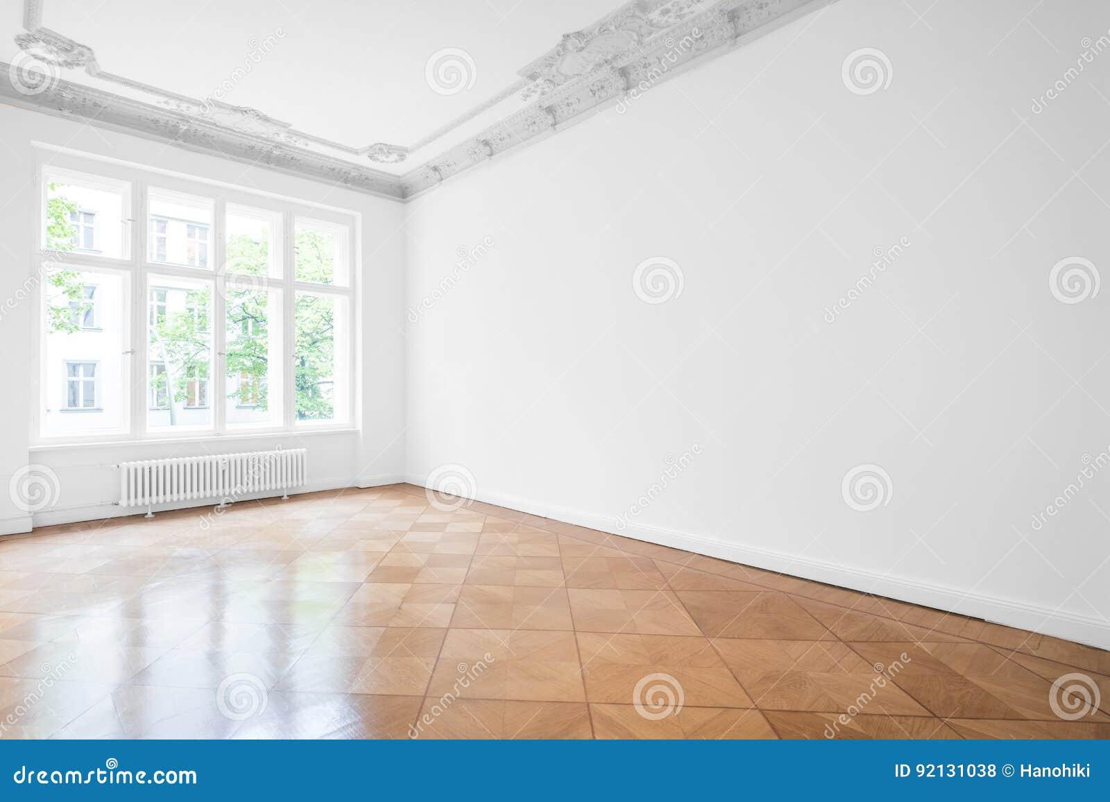 Κενό δωμάτιο με το πάτωμα παρκέ, τους άσπρους τοίχους και την οροφή στόκων
