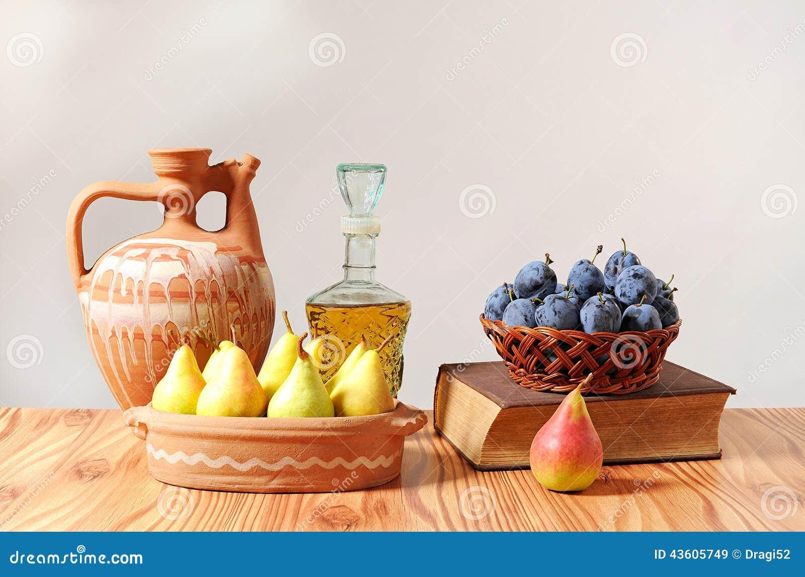 Κεραμικά καράφα και φρούτα σε ένα καλάθι