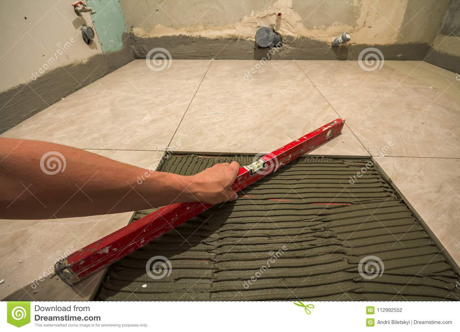 Κεραμικά κεραμίδια και εργαλεία για tiler Χέρι εργαζομένων που εγκαθιστά τα κεραμίδια πατωμάτων Εγχώρια βελτίωση, ανακαίνιση - κό