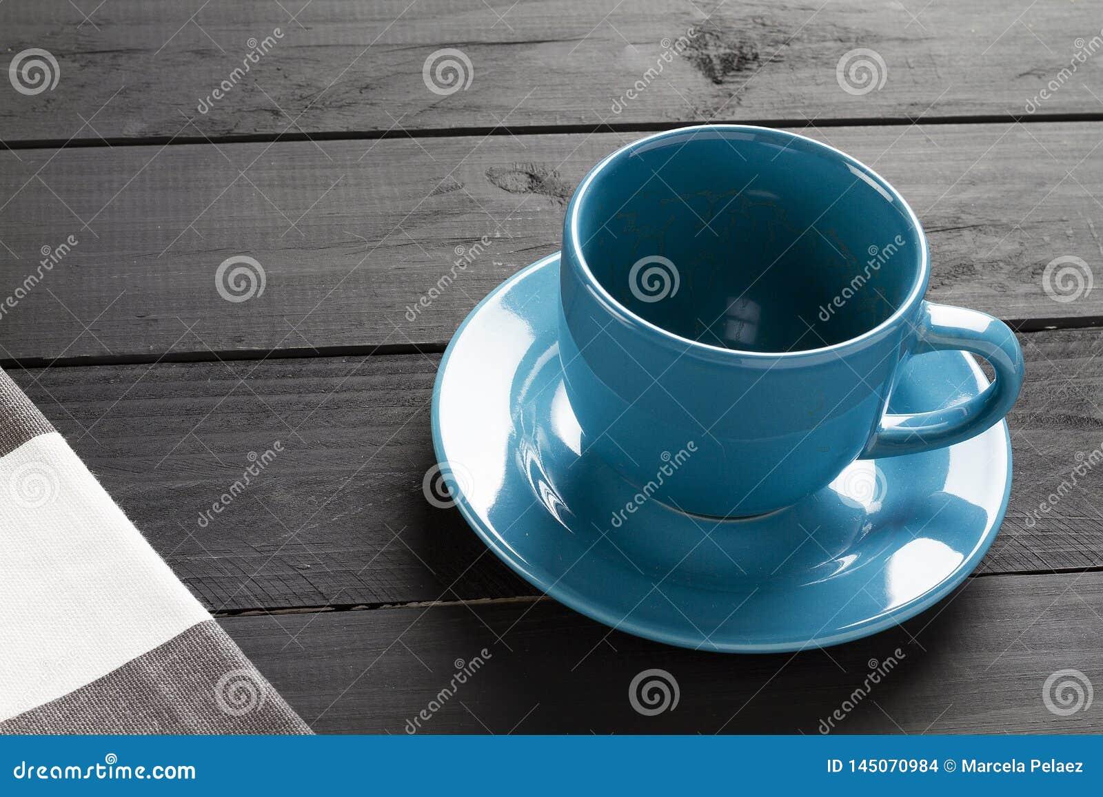 Κεραμικό φλυτζάνι για τον καφέ του μπλε χρώματος χωρίς υγρό στο μαύρο ξύλινο υπόβαθρο και το κουρέλι των γκρίζων και άσπρων λωρίδ