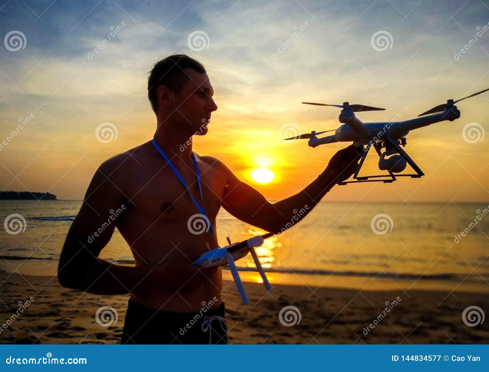 Κηφήνας που πετά στο ηλιοβασίλεμα πέρα από τη θάλασσα Άτομο που προσγε