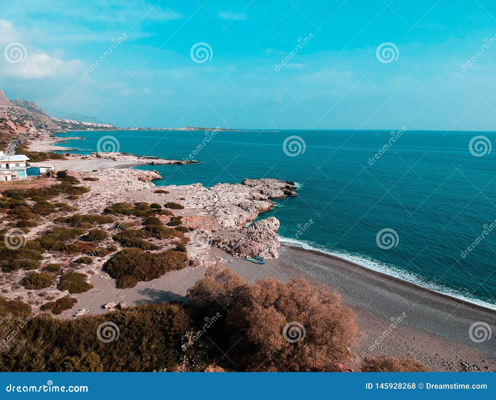 Κηφήνας που πυροβολείται στην Ελλάδα με τη συμπαθητική παραλία και την μπλε θάλασσα