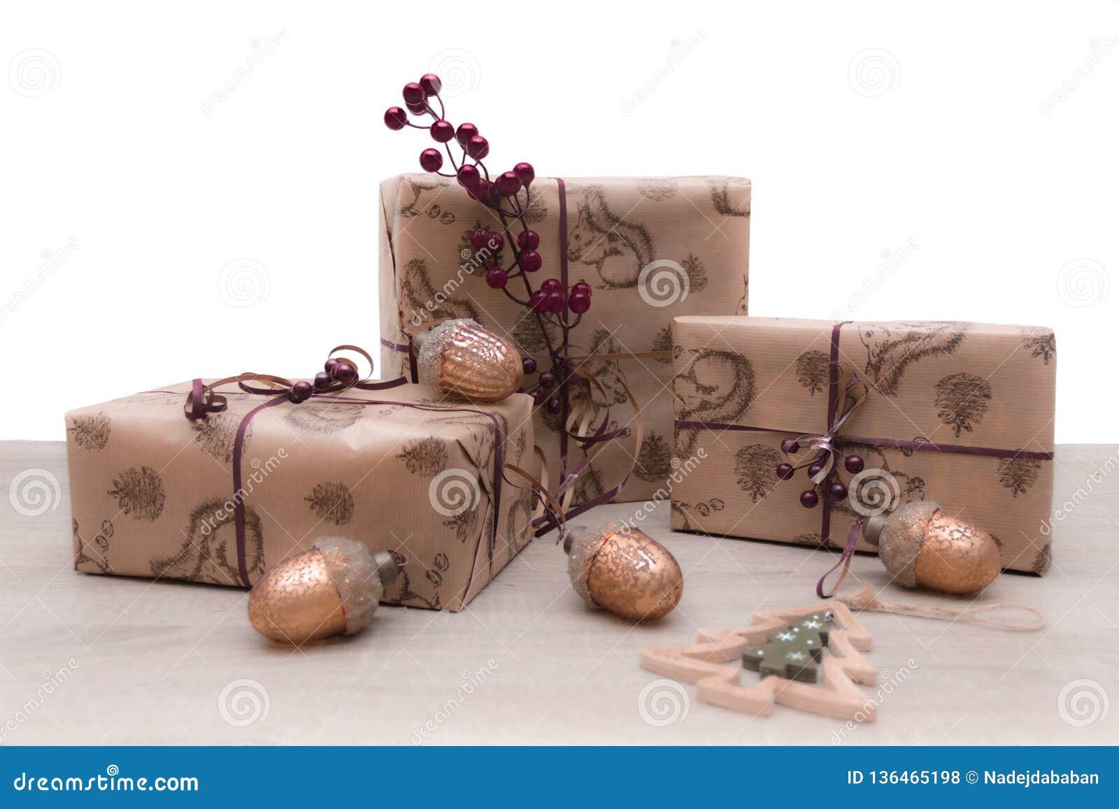 Κιβώτια δώρων Χριστουγέννων στο καφετί έγγραφο τεχνών με τα παιχνίδια γυαλιού Χριστουγέννων