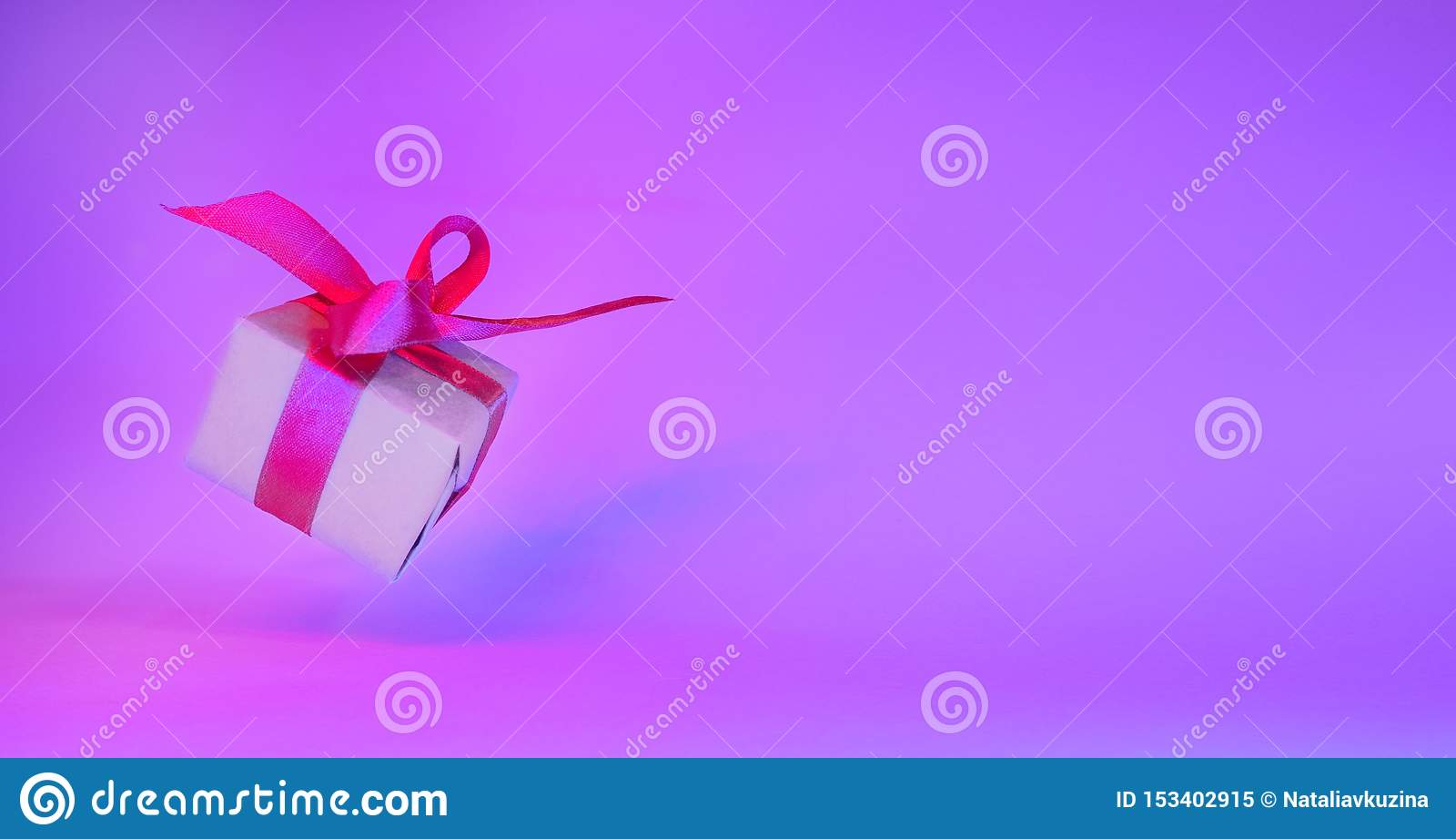 Κιβώτιο δώρων με την κόκκινη κορδέλλα στο καθιερώνον τη μόδα υπόβαθρο χρώματος νέου μηδέν έμβλημα βαρύτητας μετεωρισμός Copyspace