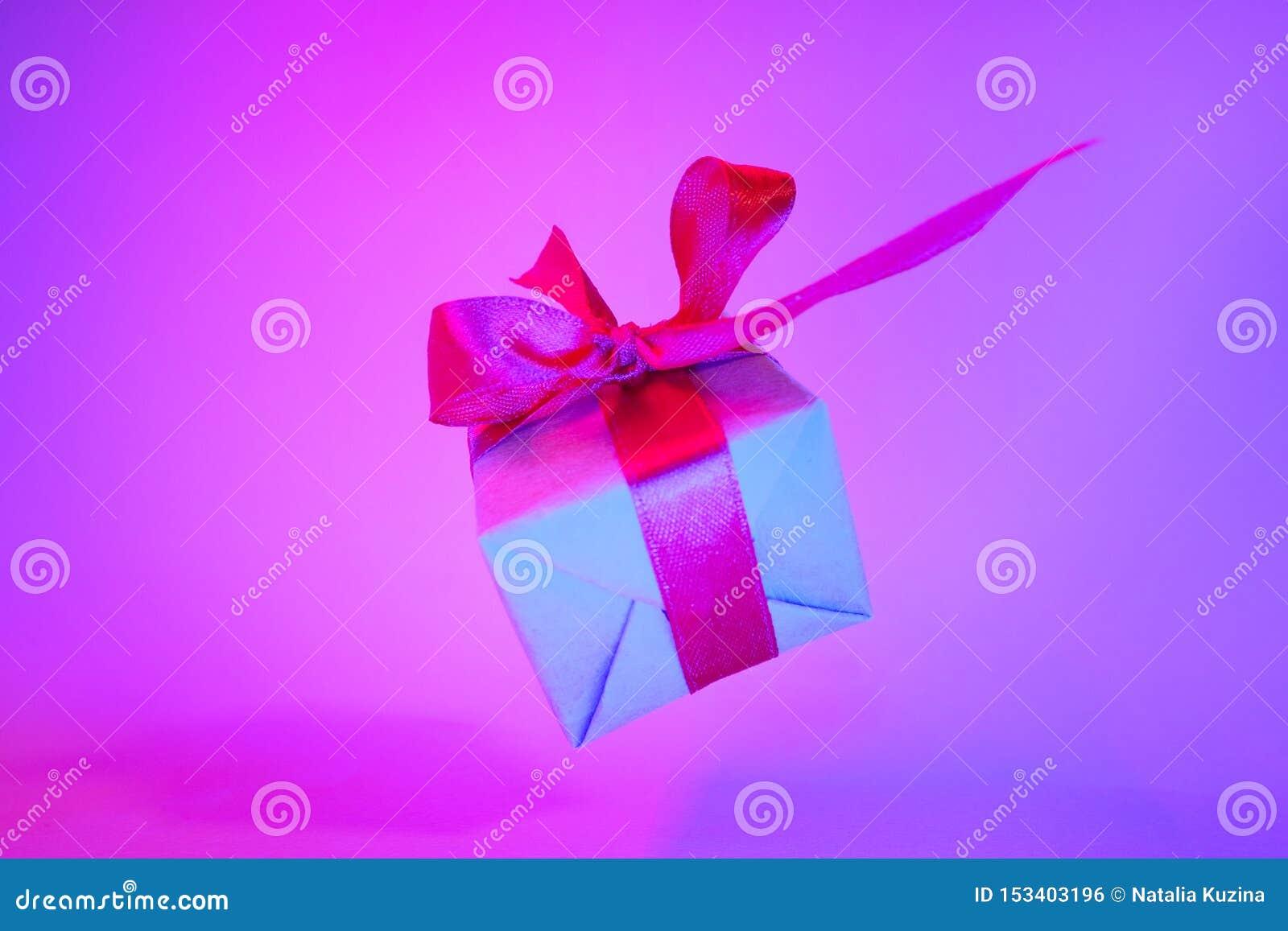 Κιβώτιο δώρων με την κόκκινη κορδέλλα στο καθιερώνον τη μόδα υπόβαθρο χρώματος νέου μηά βαρύτητα μετεωρισμός Copyspace Πωλήσεις έ