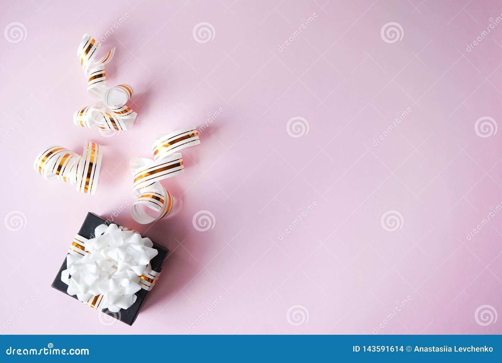 Κιβώτιο δώρων που τυλίγεται στην άσπρη και χρυσή ριγωτή κορδέλλα στο ρόδινο υπόβαθρο κρητιδογραφιών r δώρο για τα Χριστούγεννα, η