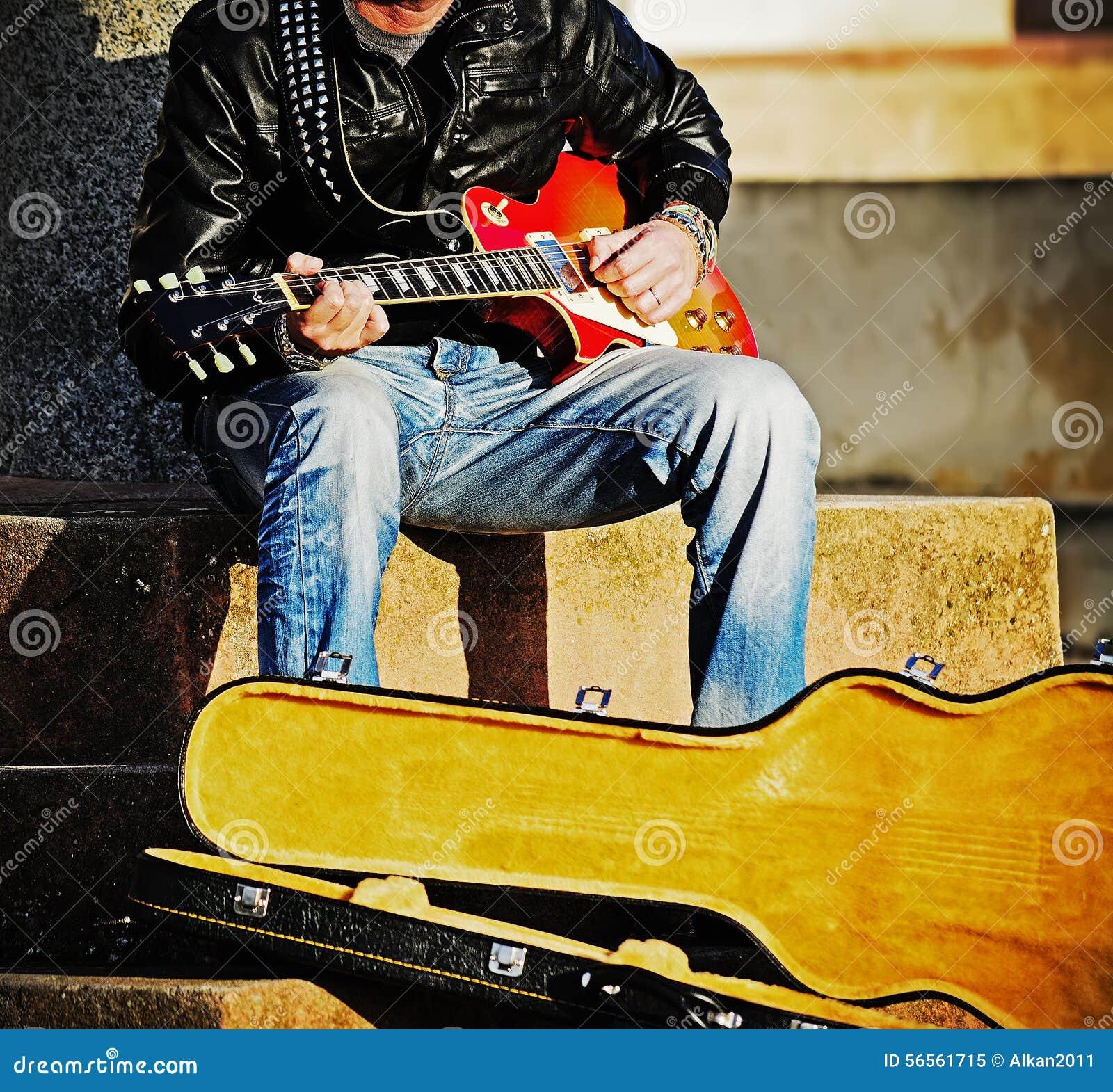 Download Κιθαρίστας με μια ανοικτή περίπτωση κιθάρων Στοκ Εικόνα - εικόνα από μελωδία, χόμπι: 56561715