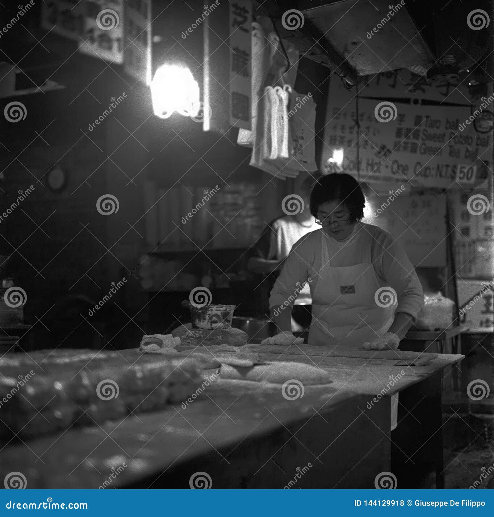 Κινεζική κυρία που προετοιμάζει τις μπουλέττες στην κουζίνα ενός εστιατορίου στην Ταϊβάν, πυροβολισμός με την αναλογική γραπτή τα