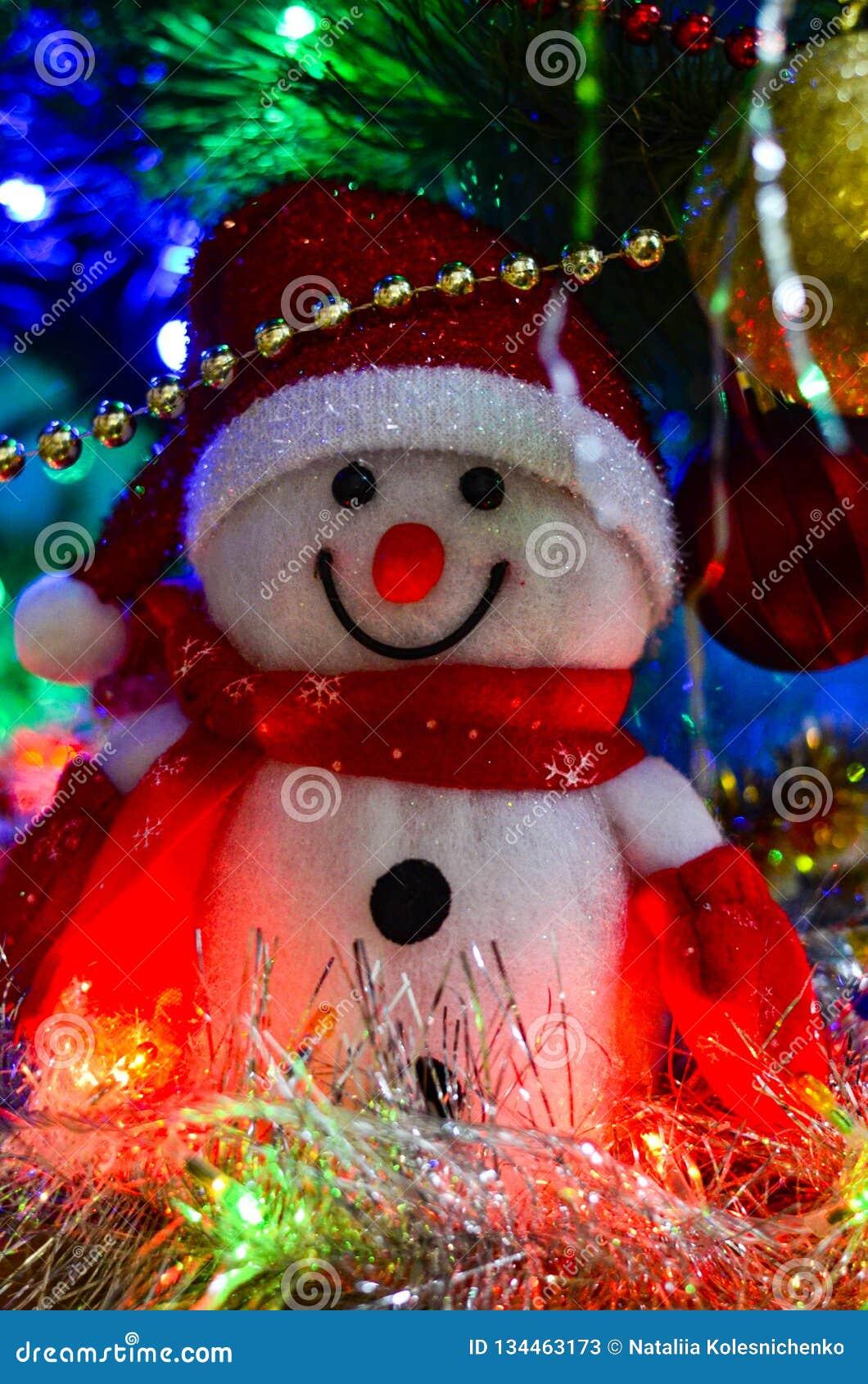 Κινηματογράφηση σε πρώτο πλάνο ενός χιονανθρώπου χειμερινών λευκού παιχνιδιών με tinsel Χριστουγέννων στο υπόβαθρο