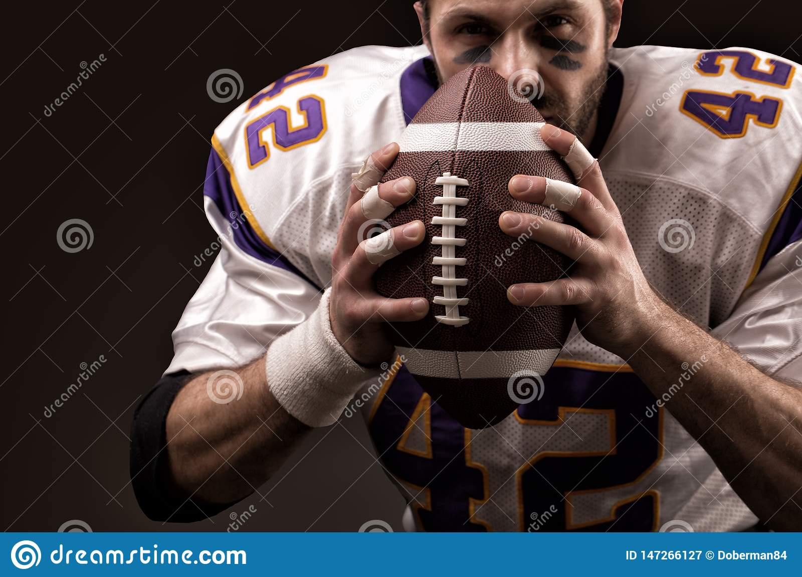 Κινηματογράφηση σε πρώτο πλάνο πορτρέτου, φορέας αμερικανικού ποδοσφαίρου, γενειοφόρος χωρίς ένα κράνος με τη σφαίρα στα χέρια το