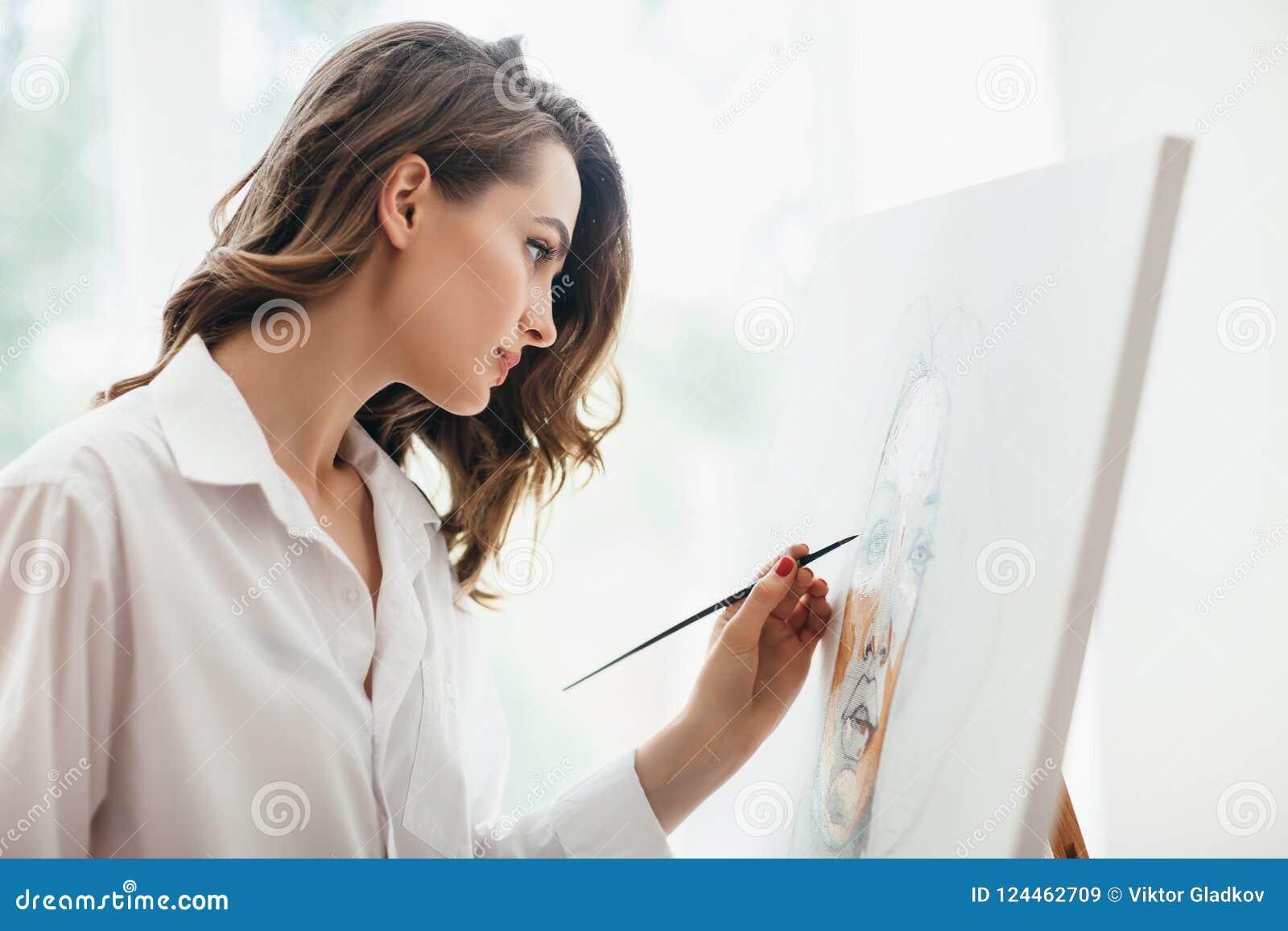 Κινηματογράφηση σε πρώτο πλάνο της νέας όμορφης ζωγραφικής γυναικών στον καμβά στο στούντιο