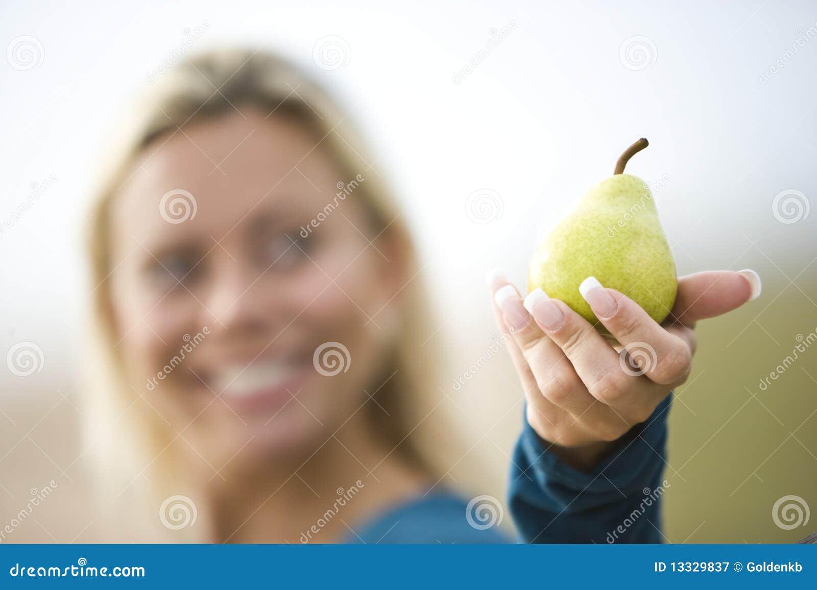 Κινηματογράφηση σε πρώτο πλάνο της χαμογελώντας γυναίκας που κρατά ένα αχλάδι