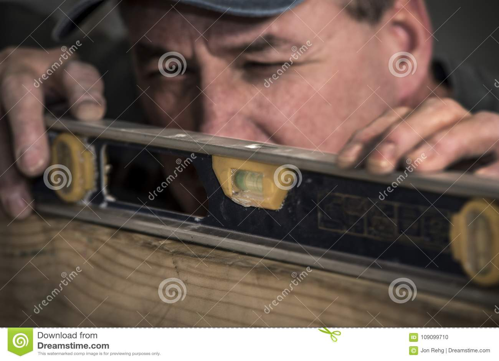 Κινηματογράφηση σε πρώτο πλάνο του αρσενικού ξυλουργού που χρησιμοποιεί το εργαλείο επιπέδων στον ξύλινο πίνακα